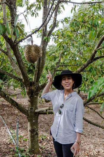 Portrait of cute woman with Durain fruit tree Casual Clothing Chaiyaphum Day Durain Farm Finger Pointing Front View Happiness Hat Leisure Activity Lifestyles Looking At Camera Nature One Person Outdoors Portrait Real People Smiling Standing Thailand Tree Tree Tropical Fruits Woman Young Women