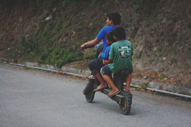 an ifugao father and his two sons ride a wooden scooter, a popular mode of transportation only found in Bananue, Philippines. Bonding Childhood Ifugao Lifestyles Local Ride Mode Of Transportation Outdoors Philippines Road Scooter The Great Outdoors - 2017 EyeEm Awards The Street Photographer - 2017 EyeEm Awards Togetherness Unique Unique Ride Wooden Scooter