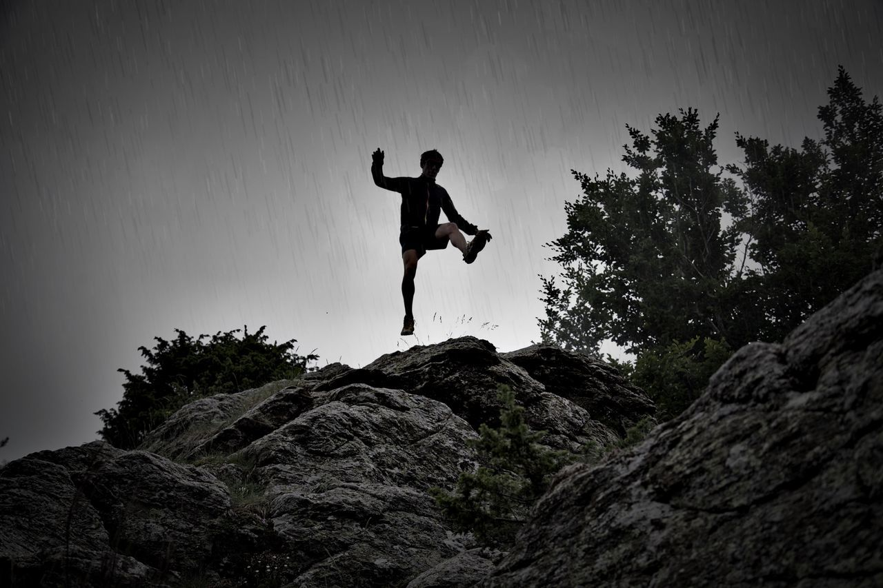 full length, mid-air, jumping, rock - object, adventure, one person, energetic, real people, leisure activity, vitality, men, nature, low angle view, lifestyles, day, outdoors, cliff, excitement, extreme sports, beauty in nature, young adult, one man only, sky, people