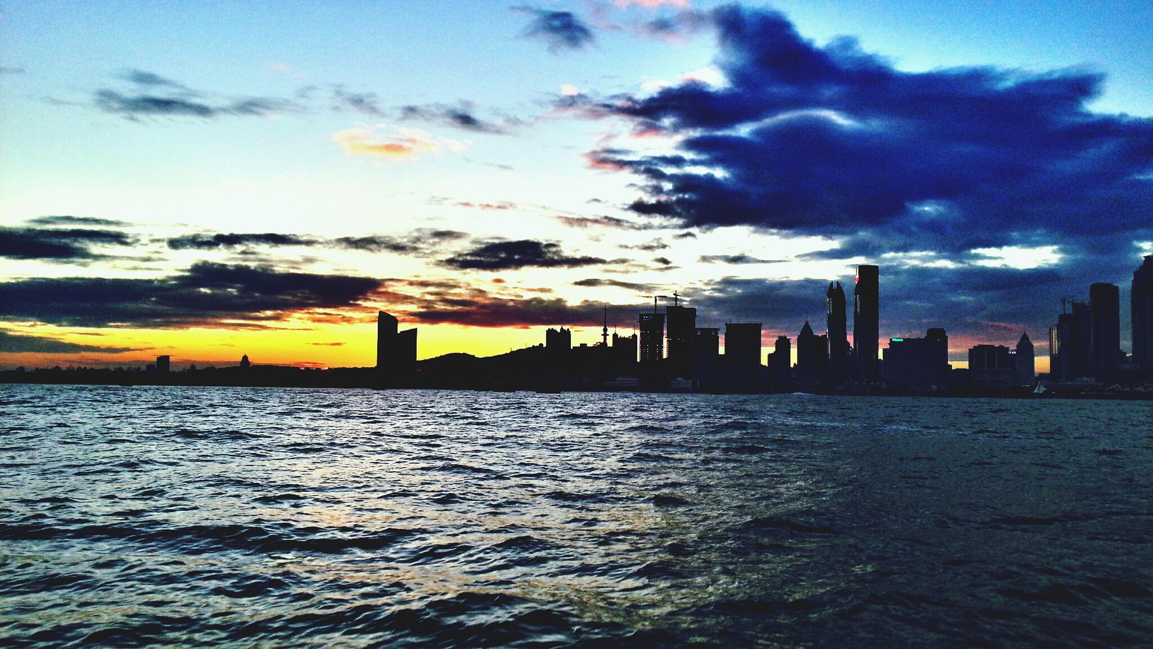 water, architecture, building exterior, built structure, waterfront, sky, city, sunset, cloud - sky, sea, skyscraper, cityscape, urban skyline, river, rippled, silhouette, cloud, skyline, scenics, tower