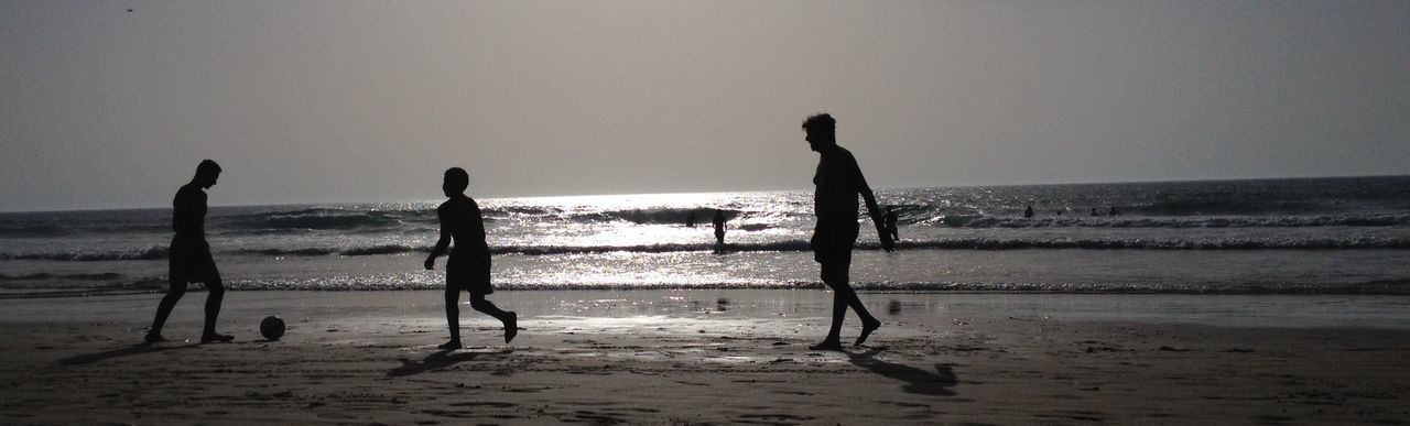 beach, sea, nature, water, silhouette, horizon over water, shore, real people, fun, sand, sky, beauty in nature, enjoyment, leisure activity, lifestyles, scenics, outdoors, clear sky, wave, standing, vacations, men, full length, day, people