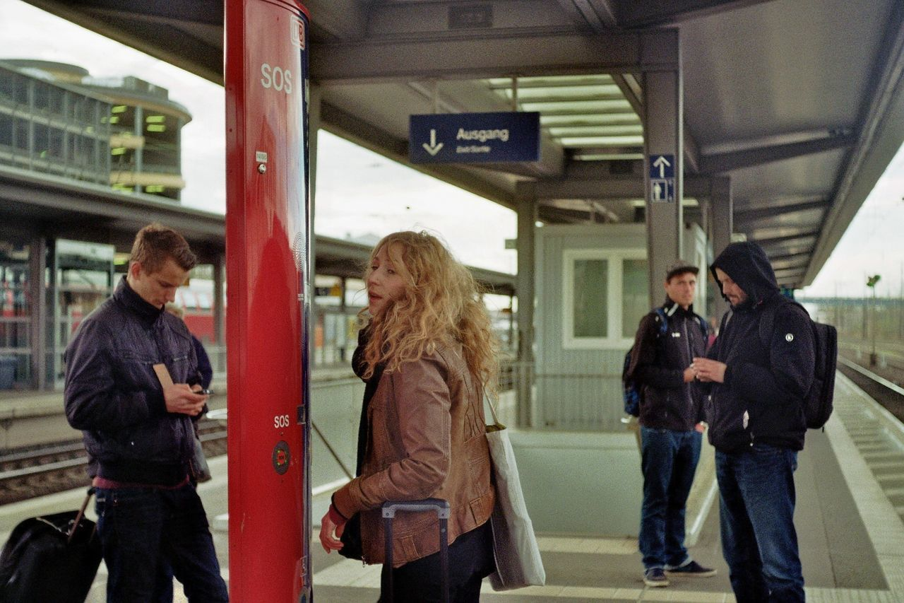 three quarter length, transportation, casual clothing, railroad station, real people, train - vehicle, public transportation, communication, standing, technology, railroad station platform, men, young adult, waiting, backpack, young men, lifestyles, mobile phone, young women, station, commuter, wireless technology, women, indoors, day, full length, subway train, time, one person, warm clothing, adult, people