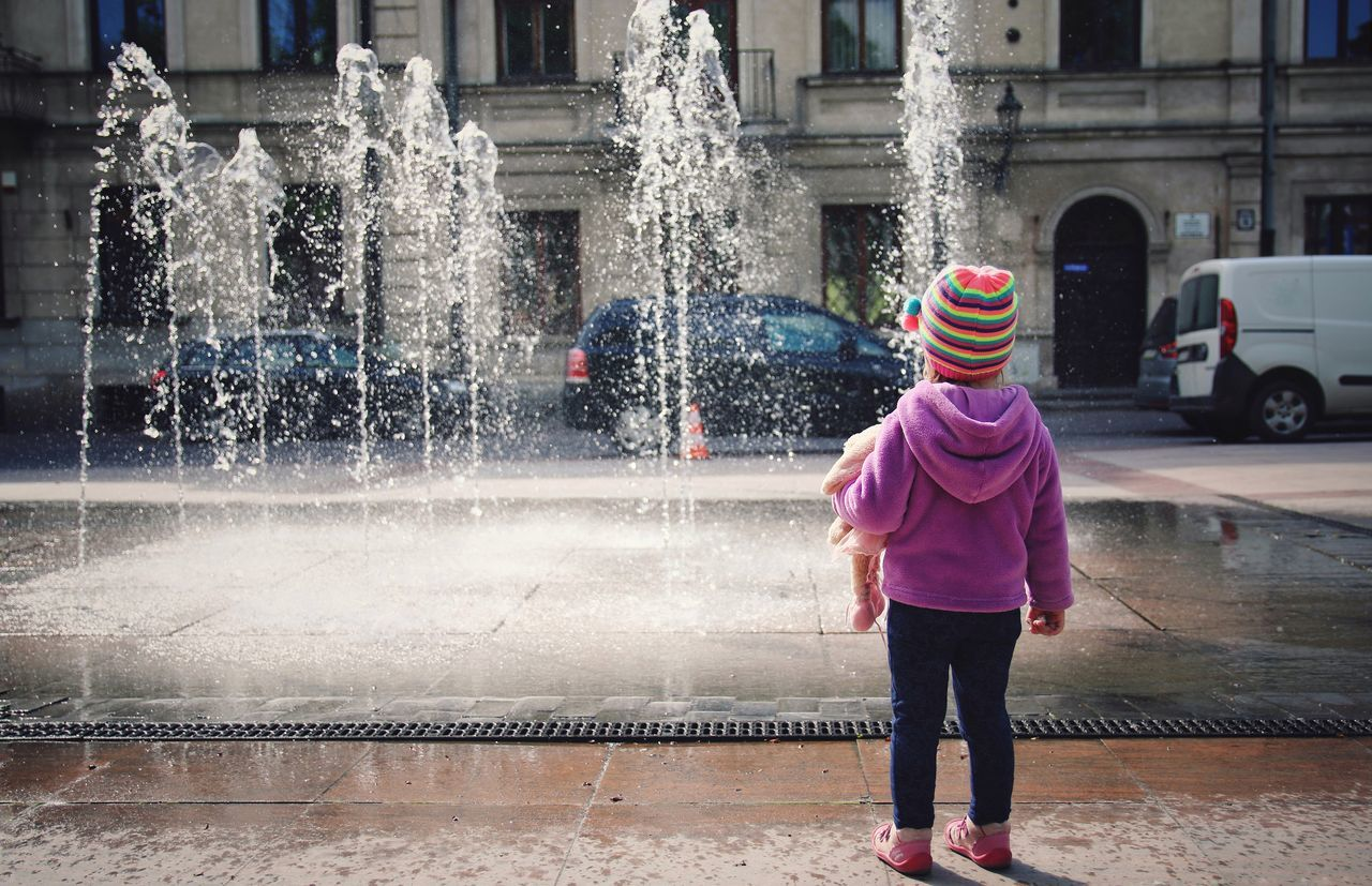 Motion Water Spraying Street Outdoors City Life Building Exterior Architecture Standing Built Structure One Person Full Length Day Real People People Kids Lifestile Portrait Toddler Girl Childhood Kids Photography Sunny Day Fontain From The Back