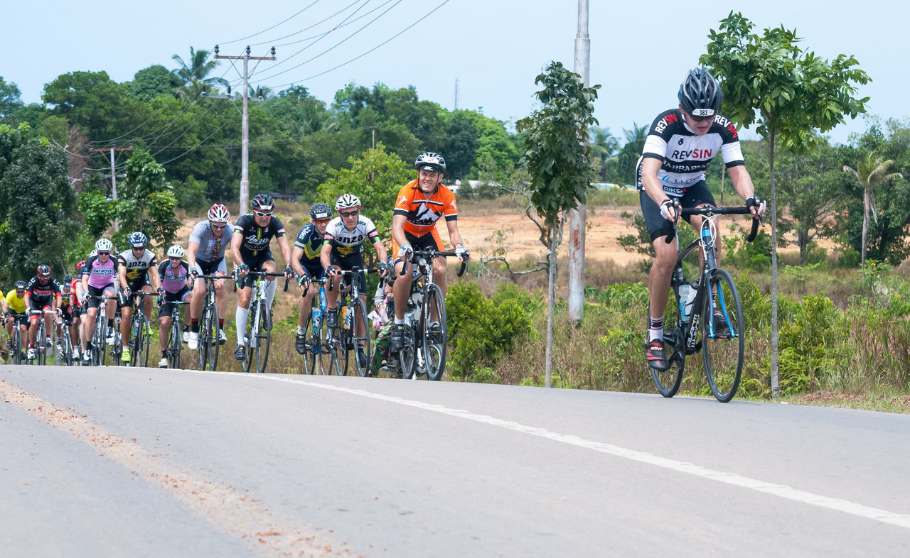 real people, transportation, sports race, sport, tree, men, day, riding, competition, large group of people, leisure activity, land vehicle, mode of transport, cycling helmet, lifestyles, bicycle, adventure, sports track, outdoors, competitive sport, sports clothing, extreme sports, nature, biker, motocross, sky, people