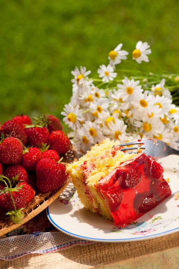 Yellow jaffa cake with strawberries and red gelatin lying on plate on wooden board in garden, bouquet of chamomile flowers behind it, vertical orientation, nobody in frame, objects in open air. Biscuit Cake Camomile Chamomiles Custard Dessert Dessert Flower Flowers Food Fruit Fruits Gelatin Jaffa Jallo Jelly No People Pie Slice Of Cake Strawberries Strawberry Sweet Sweet Food Sweet Pie Tidbits