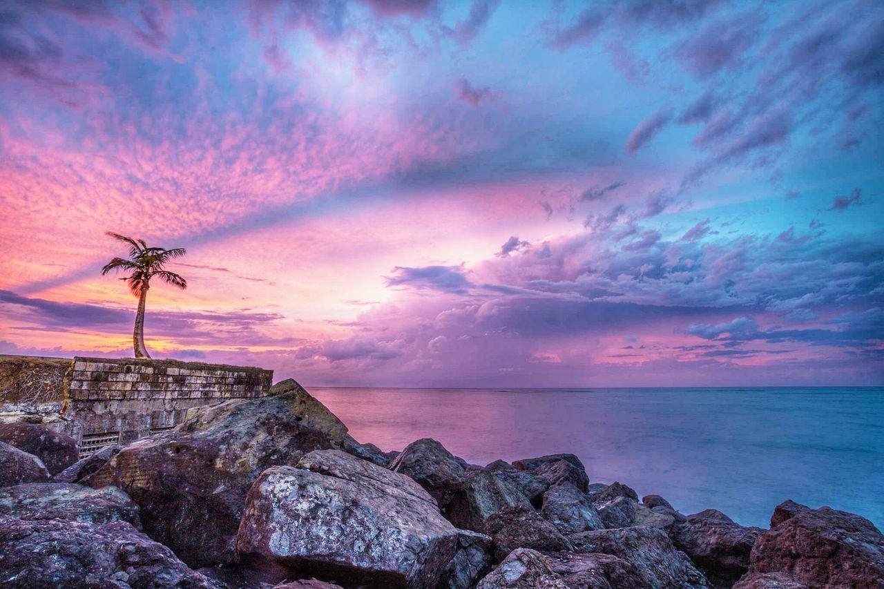 Rocks At Seaside Against Cloudy Sky
