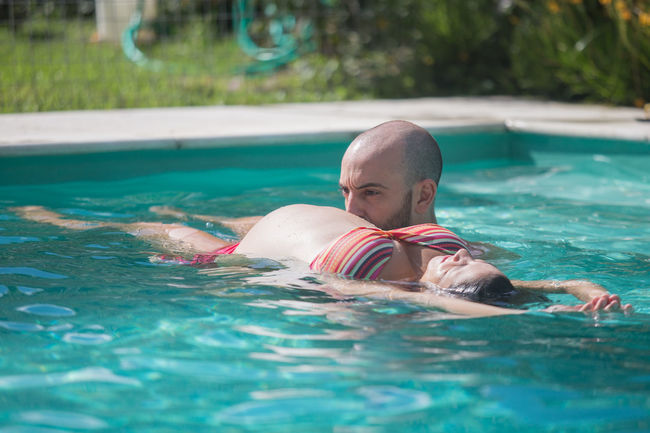 Pregnant girl floating in the water along with his husband in a swimming pool Baby Blue Casual Clothing Cute Day Enjoyment Family Focus On Foreground Fun Leisure Activity Lifestyles Love Mother Mothernature Mothersday Nature Outdoors Pregnant Relaxation Swimming Swimming Pool Swimmingpool Turquoise Colored Vacations Water