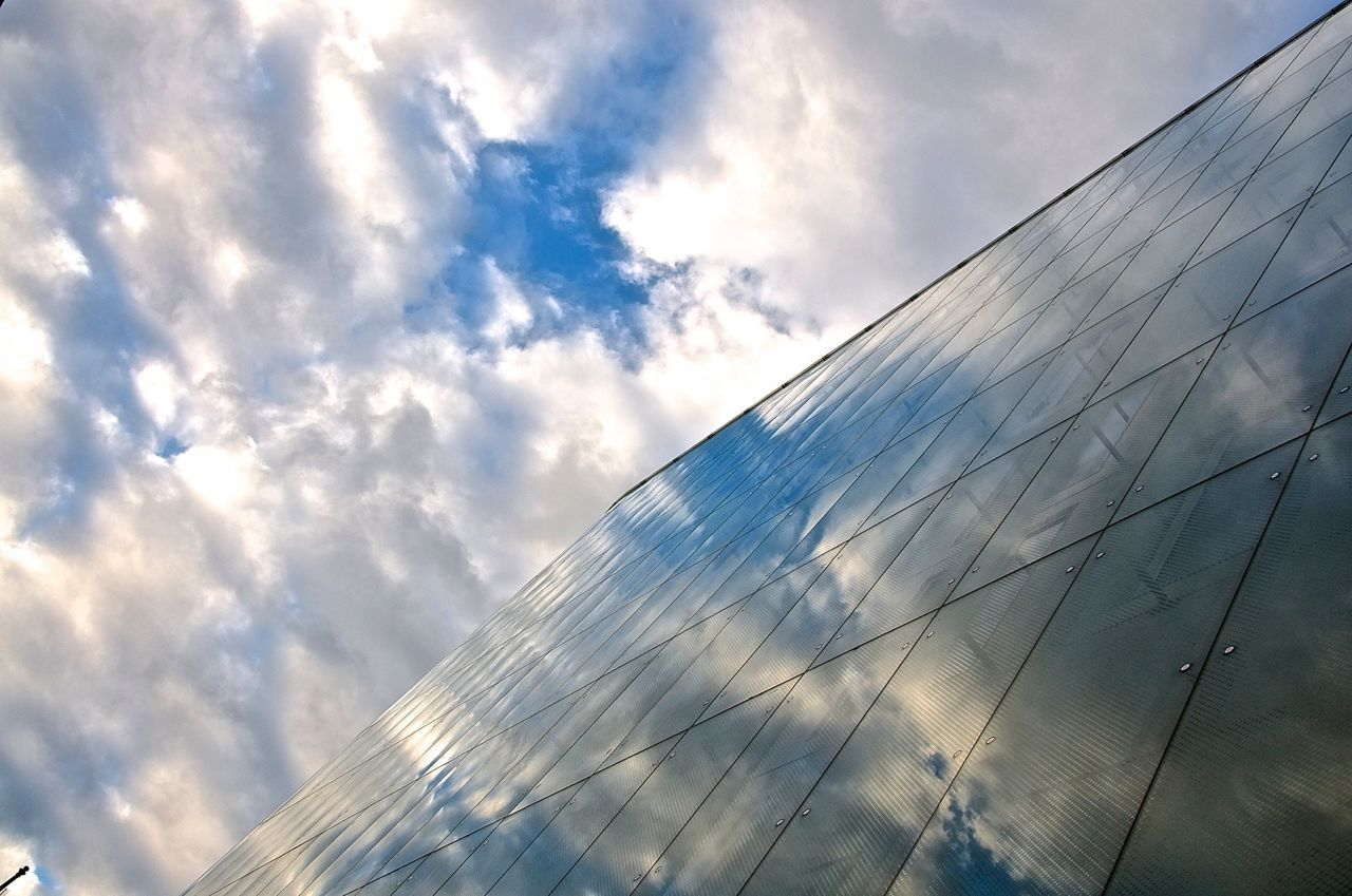 Low Angle View Of Modern Building With Clouds Reflection