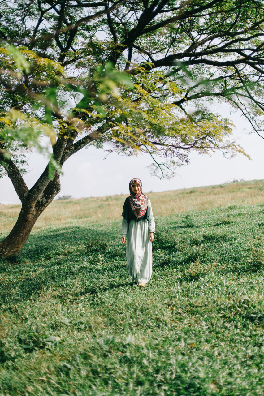 tree, field, nature, front view, real people, growth, lifestyles, grass, young women, traditional clothing, leisure activity, looking at camera, day, standing, green color, outdoors, one person, smiling, young adult, portrait, women, full length, beauty in nature, branch, happiness, landscape, flower, sky