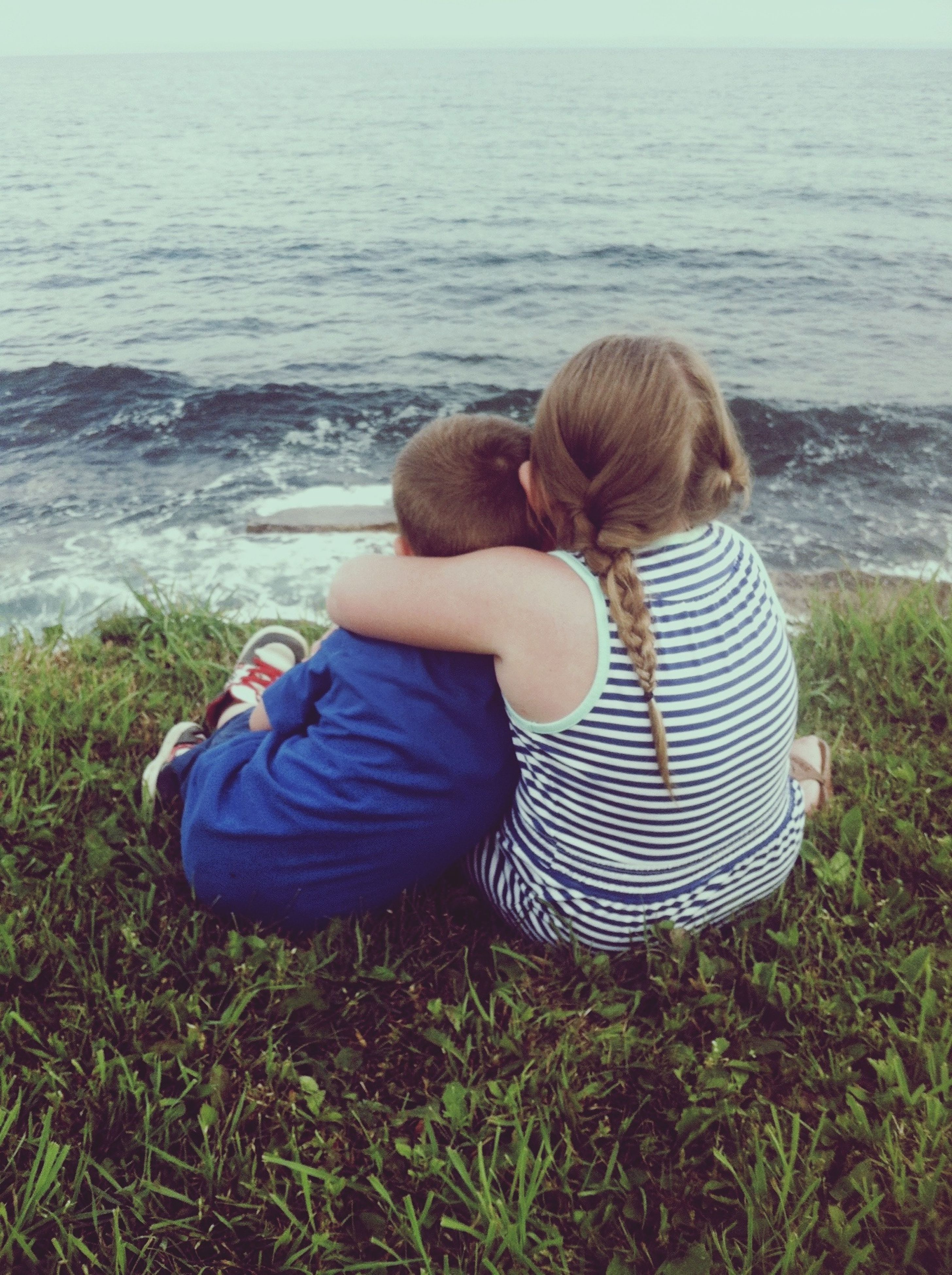 childhood, water, leisure activity, sea, lifestyles, rear view, elementary age, casual clothing, girls, full length, grass, sitting, relaxation, boys, innocence, beach, person, shore