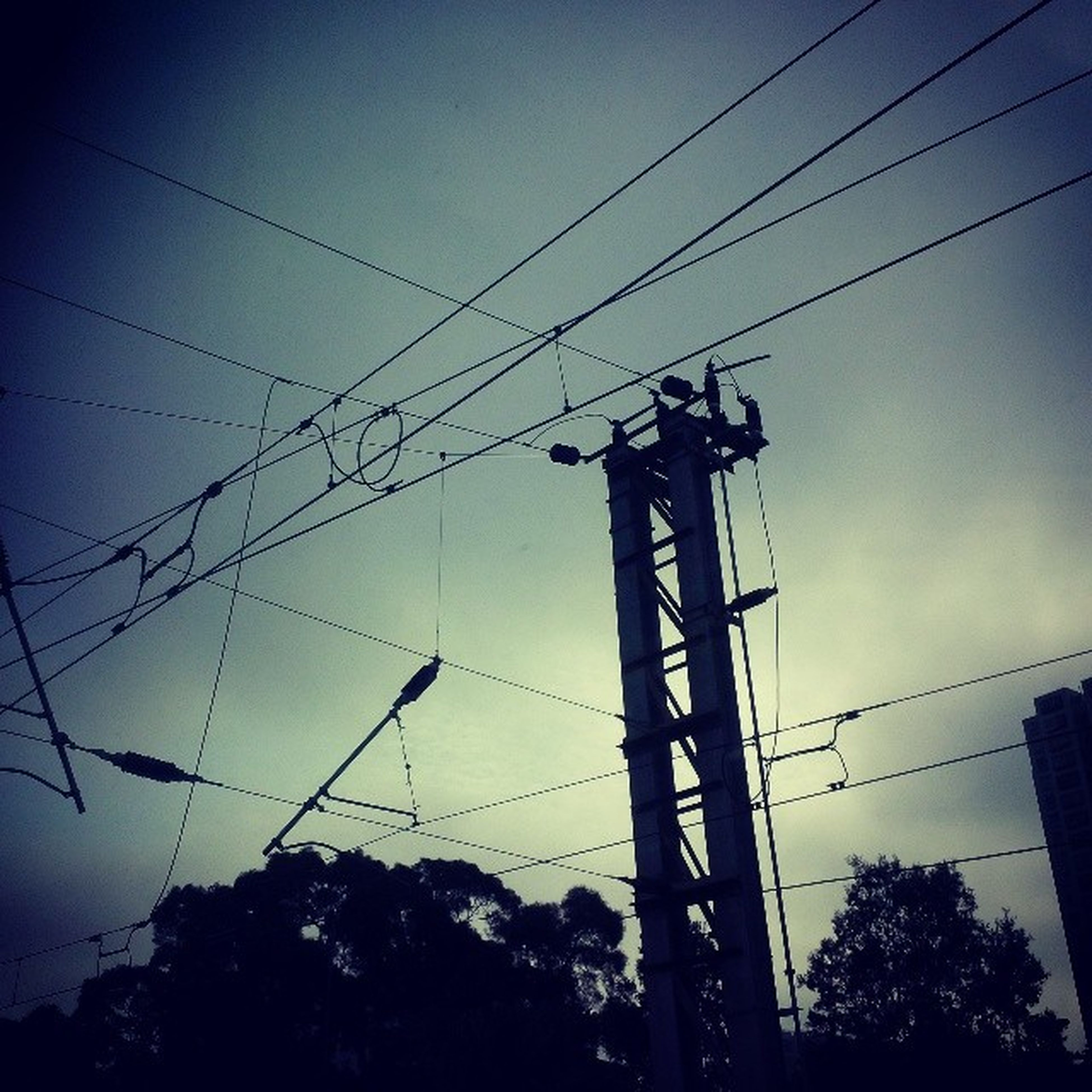 power line, low angle view, power supply, electricity pylon, electricity, silhouette, cable, connection, technology, fuel and power generation, sky, power cable, dusk, street light, pole, lighting equipment, blue, outdoors, tree, no people