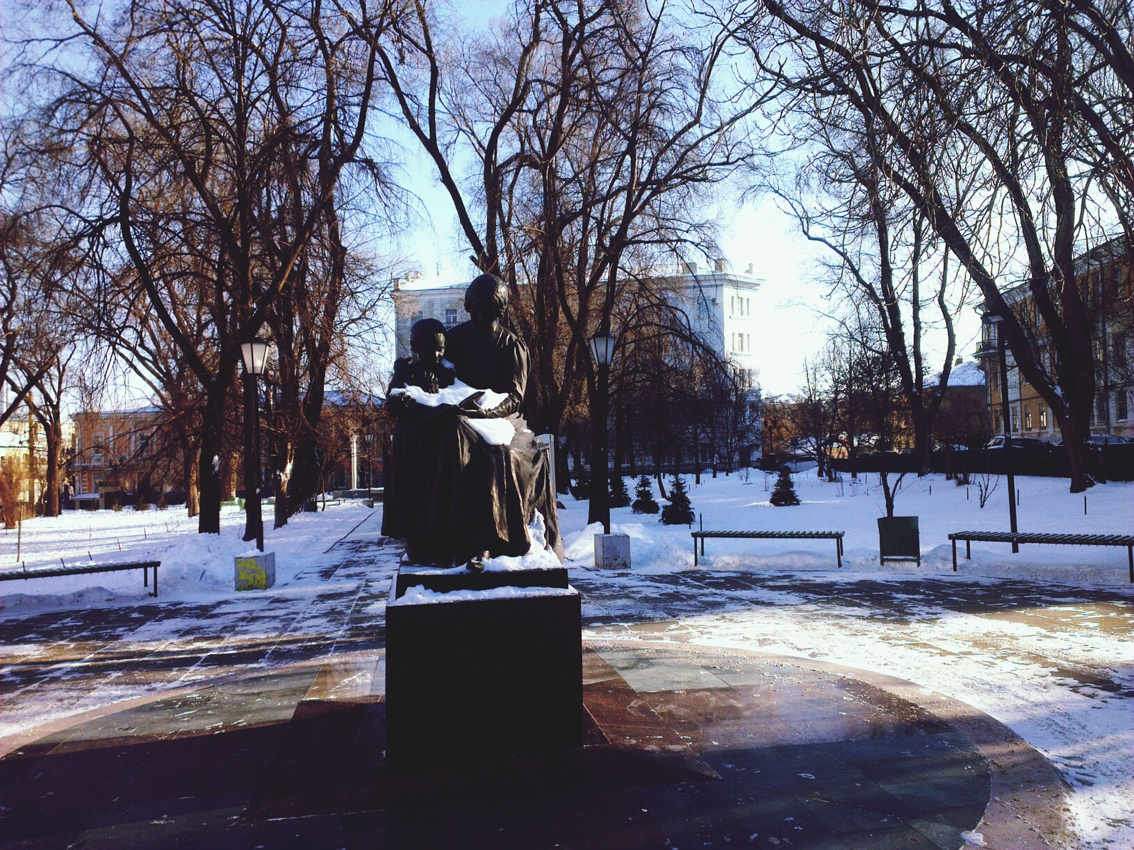 tree, building exterior, built structure, architecture, bare tree, snow, winter, cold temperature, city, season, sky, water, frozen, street, incidental people, day, branch, outdoors, fountain, park - man made space