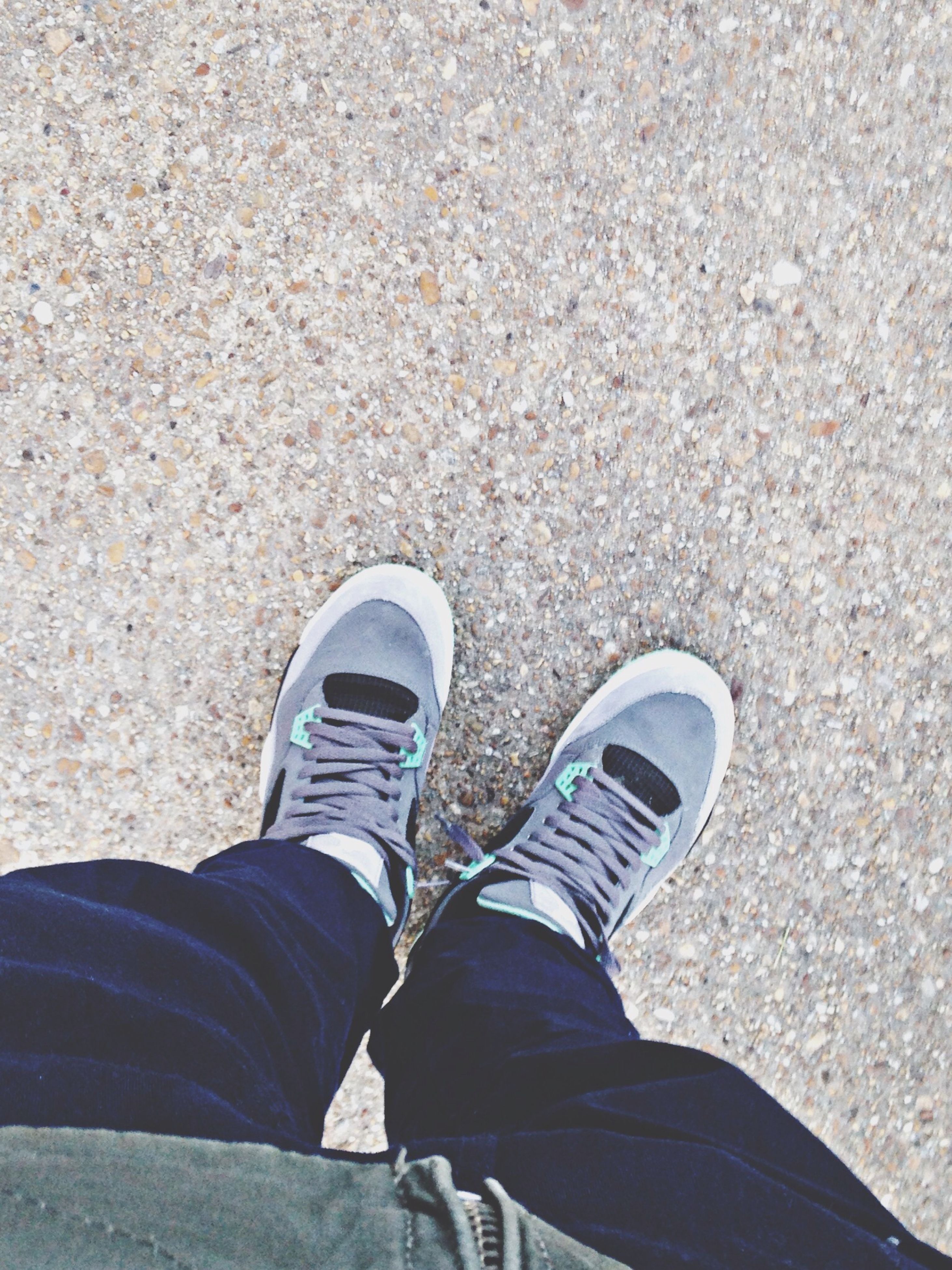 low section, person, shoe, personal perspective, standing, footwear, lifestyles, jeans, high angle view, human foot, leisure activity, men, casual clothing, directly above, canvas shoe, street, day