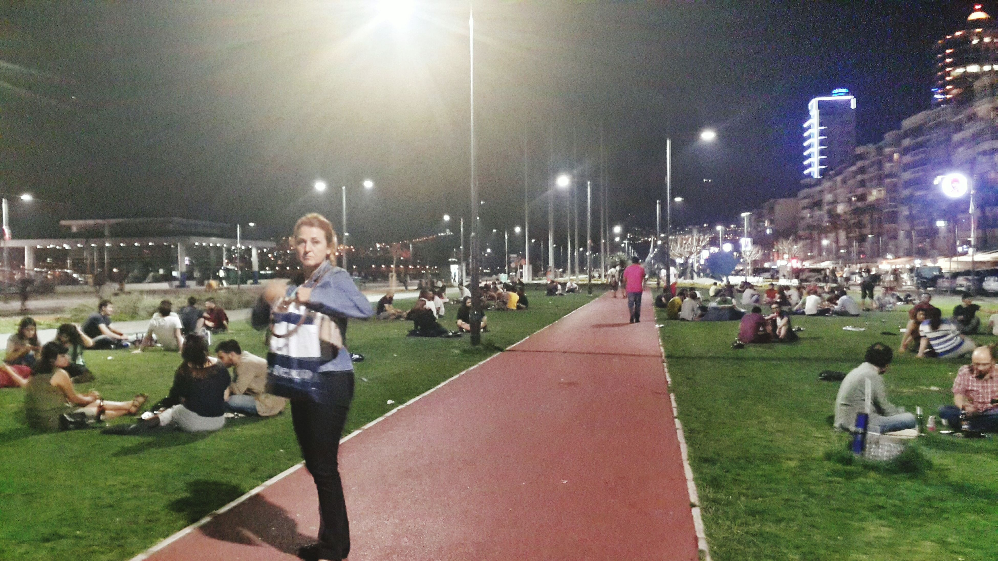 large group of people, grass, men, person, lifestyles, leisure activity, park - man made space, sport, lawn, city life, street light, crowd, mixed age range, sitting, city, night, outdoors, illuminated, green color