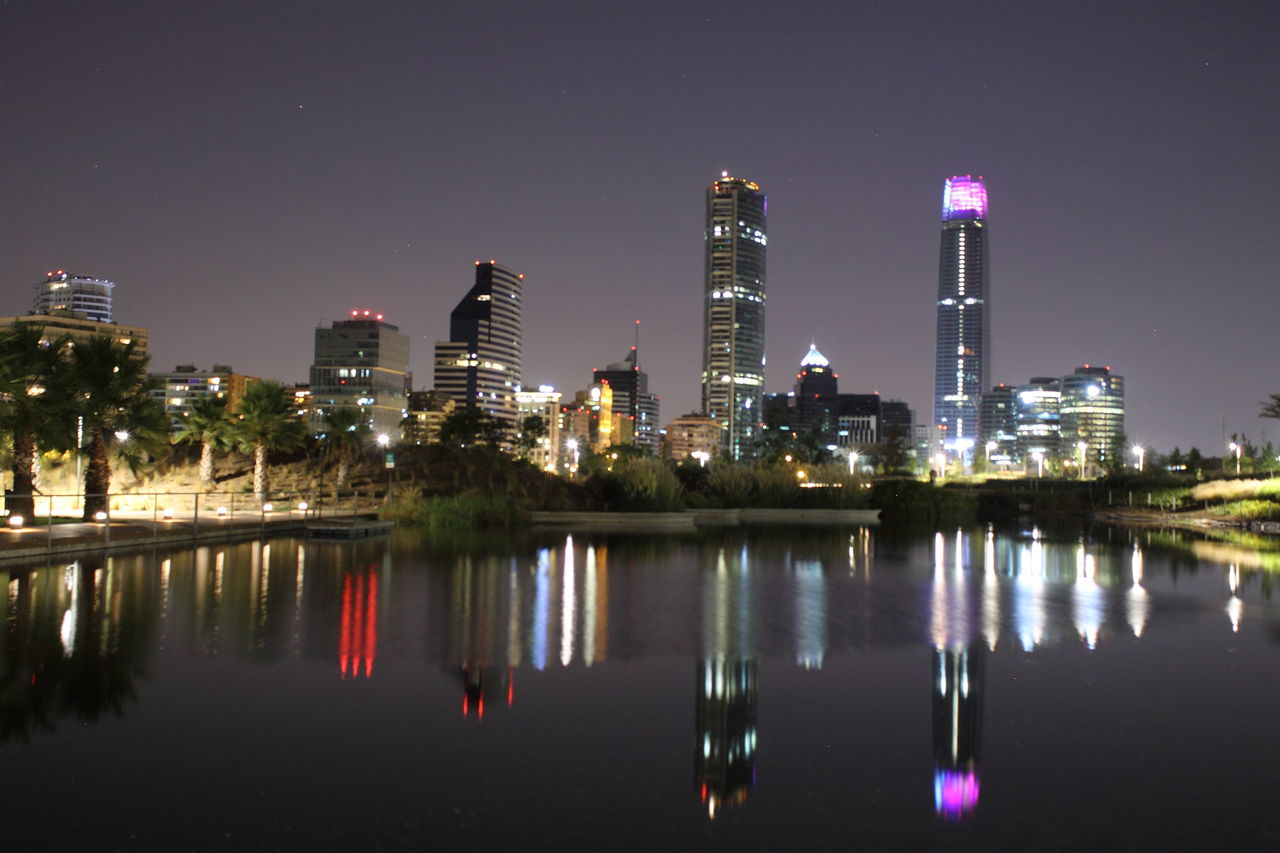 building exterior, night, illuminated, architecture, built structure, reflection, skyscraper, no people, tall, waterfront, city, smoke stack, sky, outdoors, water, modern