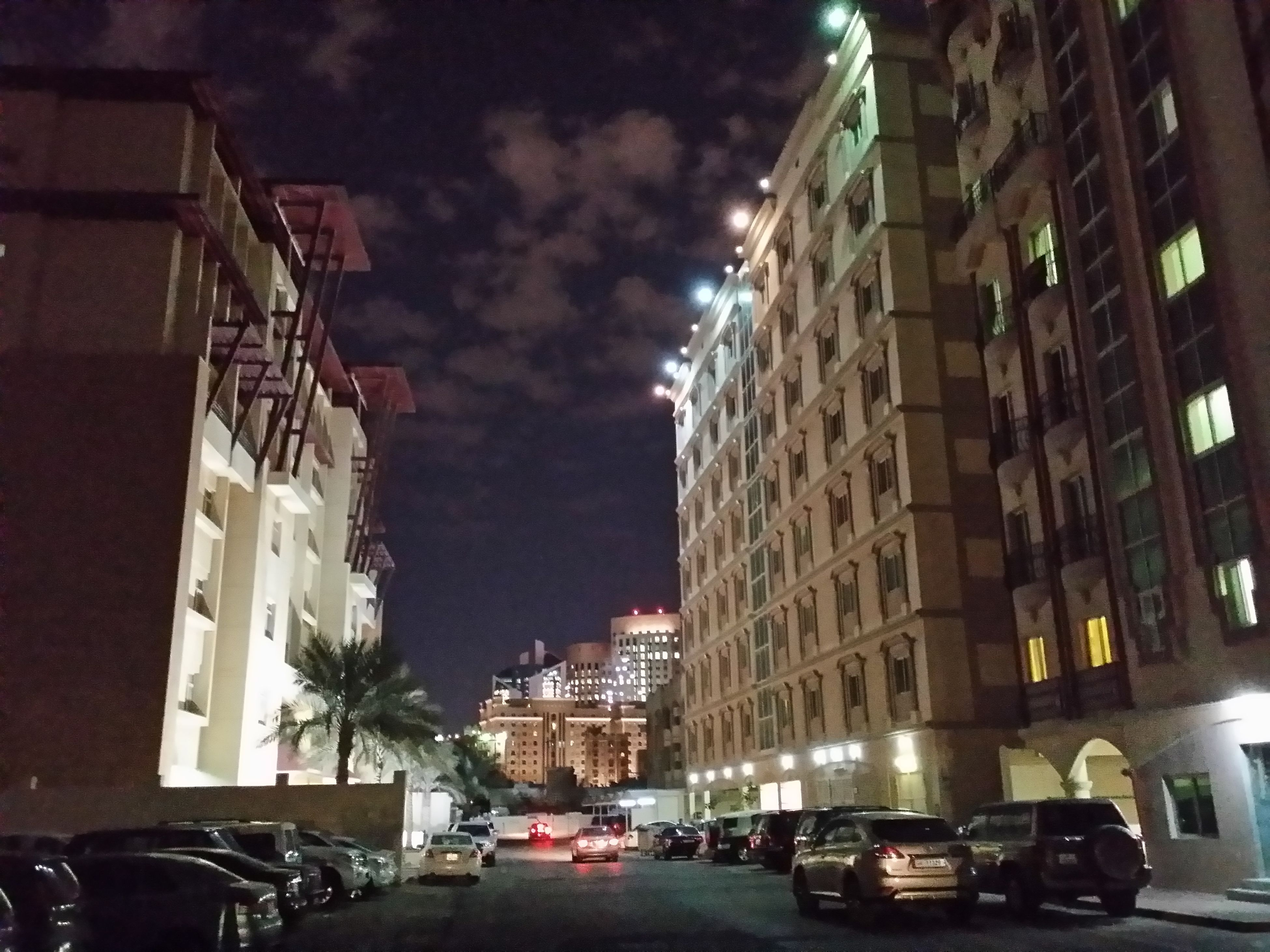 building exterior, car, architecture, land vehicle, transportation, built structure, mode of transport, street, city, sky, road, building, traffic, city street, illuminated, residential building, cloud - sky, parking, night, residential structure