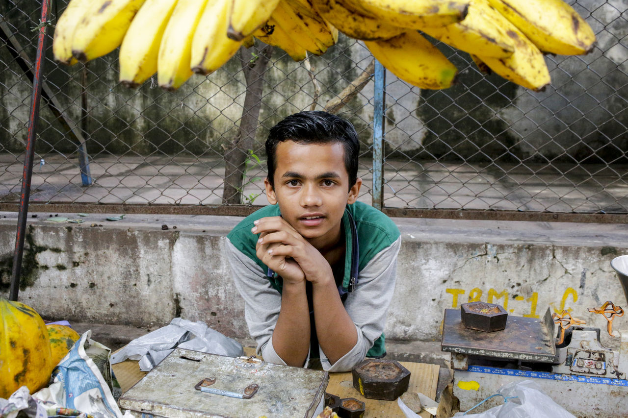 A young man at a market stall selling bananas in Ujjain, India ASIA Banana Bananas Boy Fruit India Landscape Portrait Market Natural Natural Light Portrait One Person Outdoors Outside Portrait Real People Stall Travel Travel Photography Ujjain