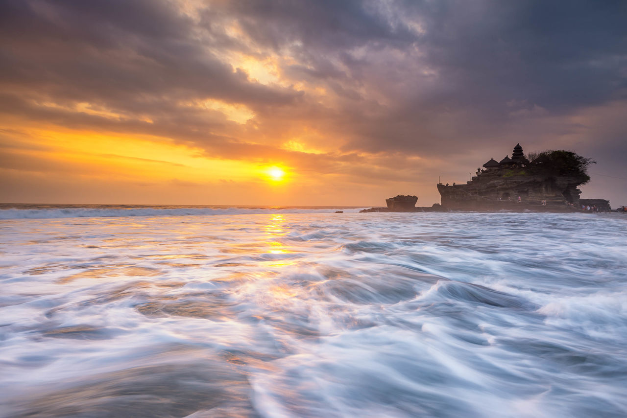 Sunset at Tanah Lot, a popular tourist attraction in Bali, Indonesia. Architecture Architecture Bali Beach Cloud - Sky Clouds Clouds And Sky Cloudscape INDONESIA Island Moss Nature Outdoors Pura Rock Formation Sea Sunset Sunsets Tanah Lot Temple Tourist Tourist Attraction  Travel Travel Destinations Waves