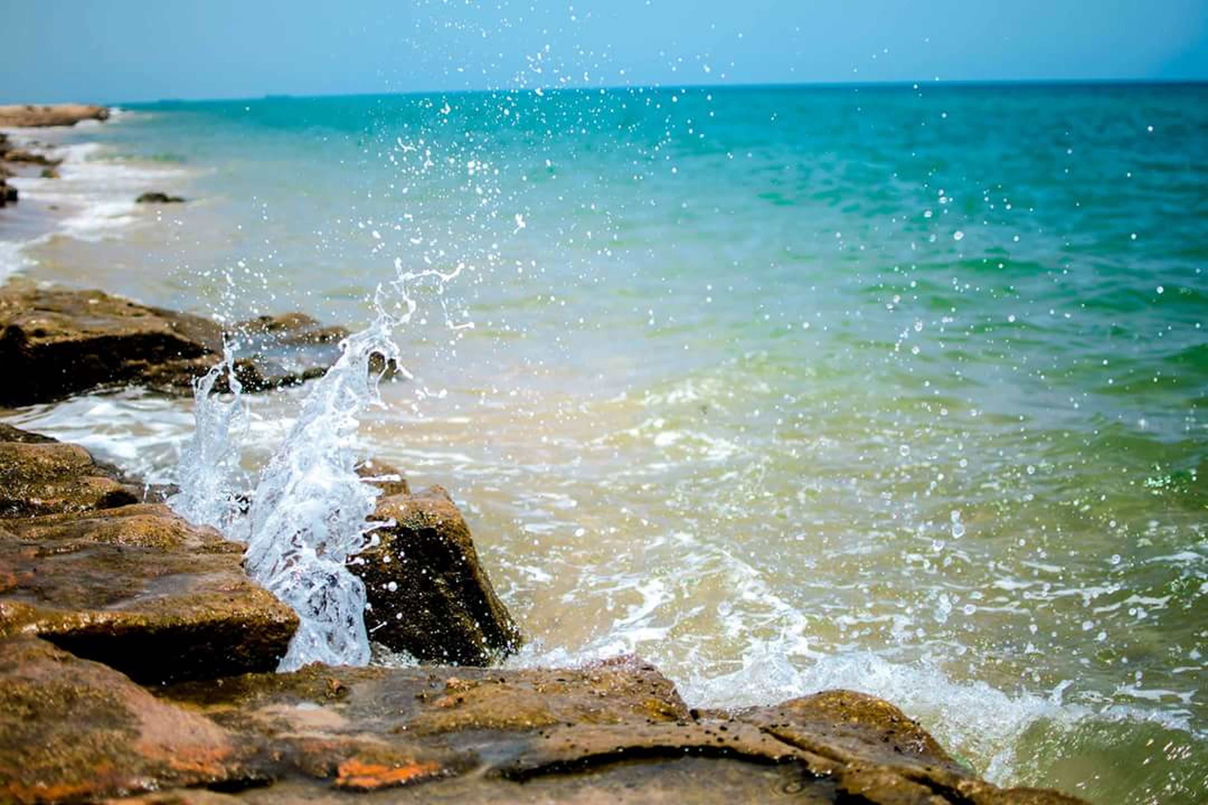 water, sea, horizon over water, wave, scenics, beach, surf, beauty in nature, shore, tranquil scene, tranquility, nature, rock - object, motion, idyllic, blue, rock formation, coastline, splashing, sky