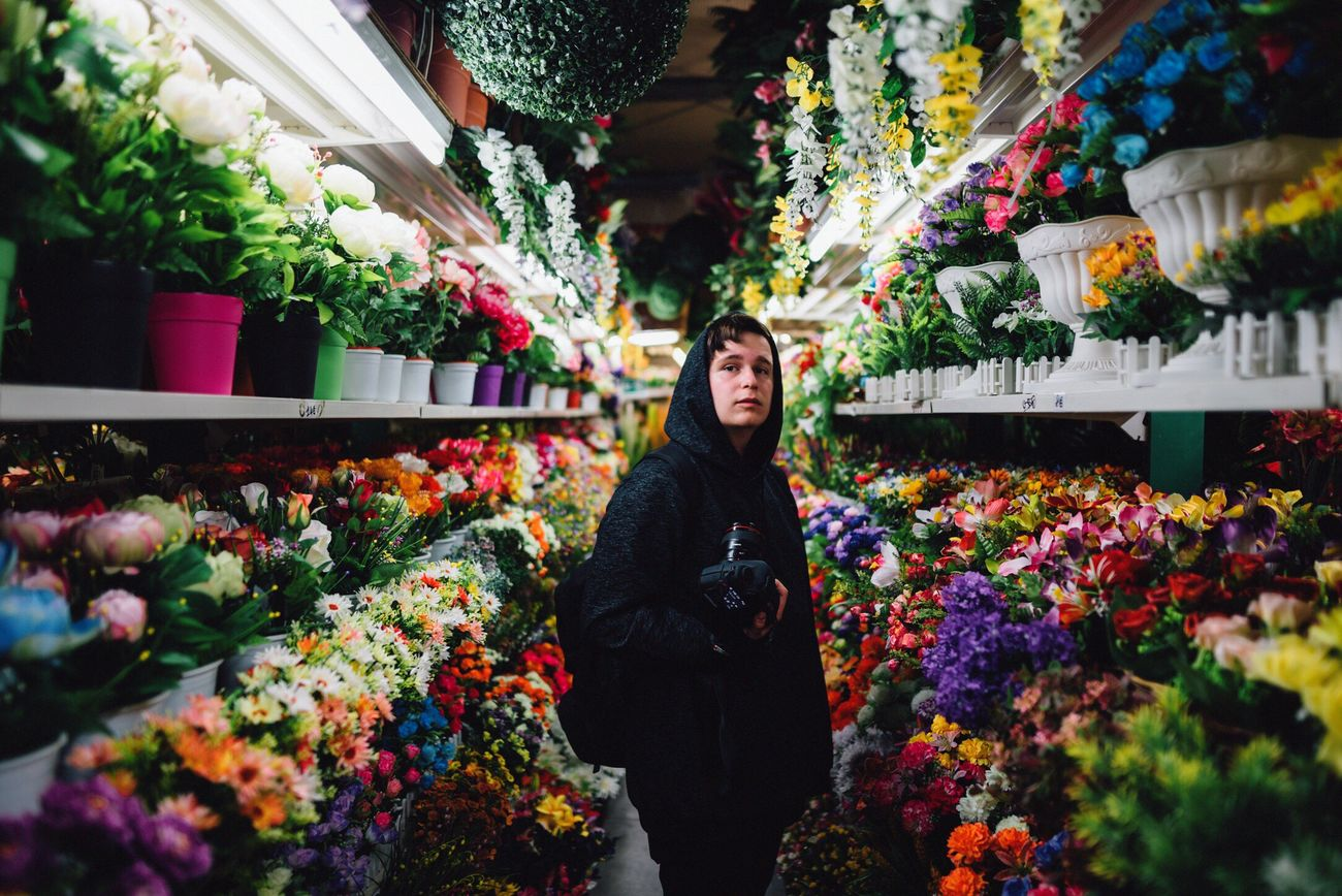 Flowerboy Flower Retail  Multi Colored Freshness Flower Shop Small Business Store Choice Flower Market Customer  Florist Beauty In Nature One Person Consumerism Shootermag The Portraitist - 2017 EyeEm Awards Lowlight Streetphotography EyeEm Best Shots EyeEm Gallery Fragility Looking At Camera One Man Only Portrait