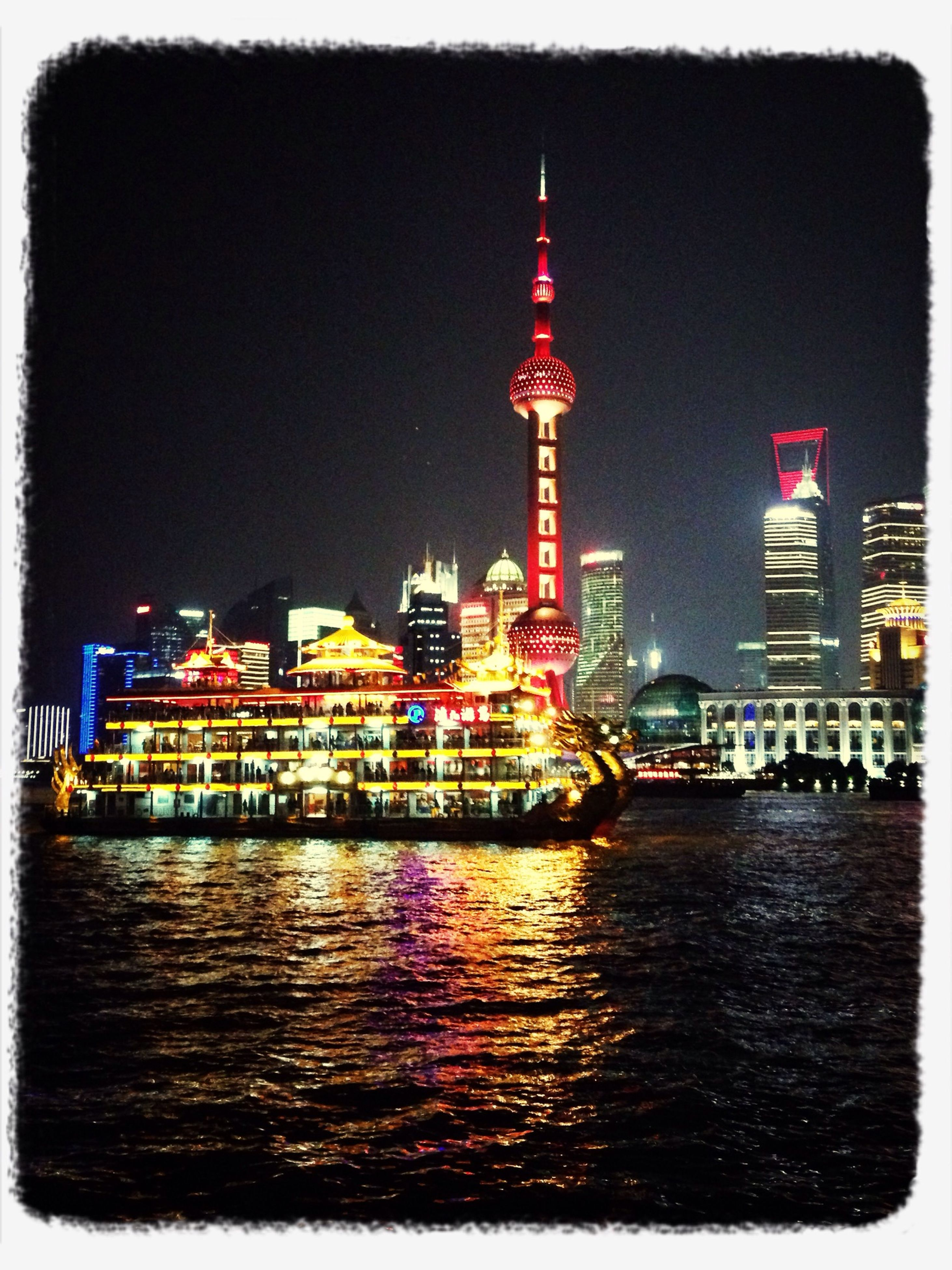 architecture, building exterior, built structure, transfer print, city, waterfront, illuminated, auto post production filter, water, tower, river, night, cityscape, clear sky, skyscraper, tall - high, capital cities, travel destinations, sky, reflection