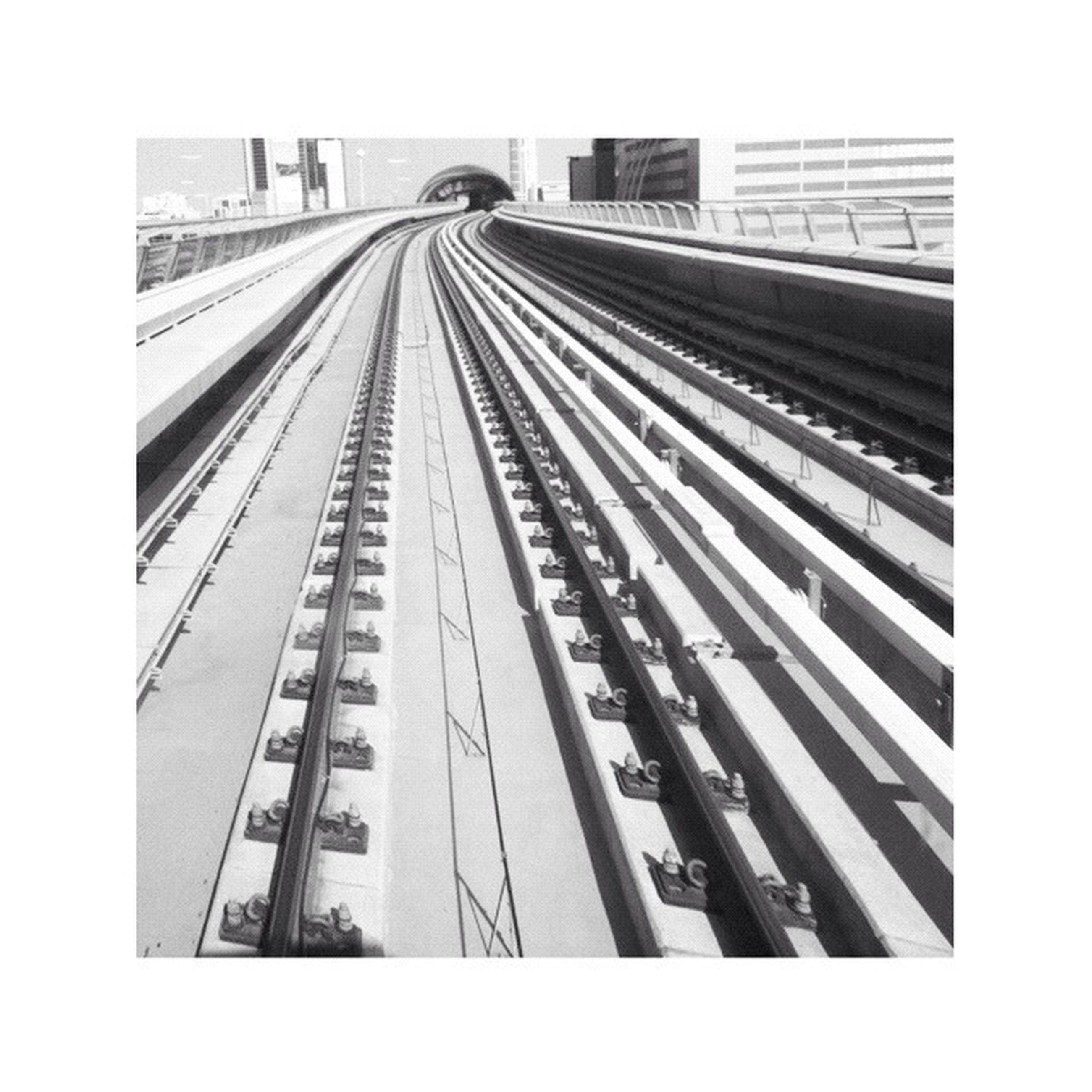 transfer print, auto post production filter, architecture, built structure, diminishing perspective, transportation, railroad track, connection, the way forward, city, sky, vanishing point, rail transportation, clear sky, building exterior, day, outdoors, bridge - man made structure, no people, long