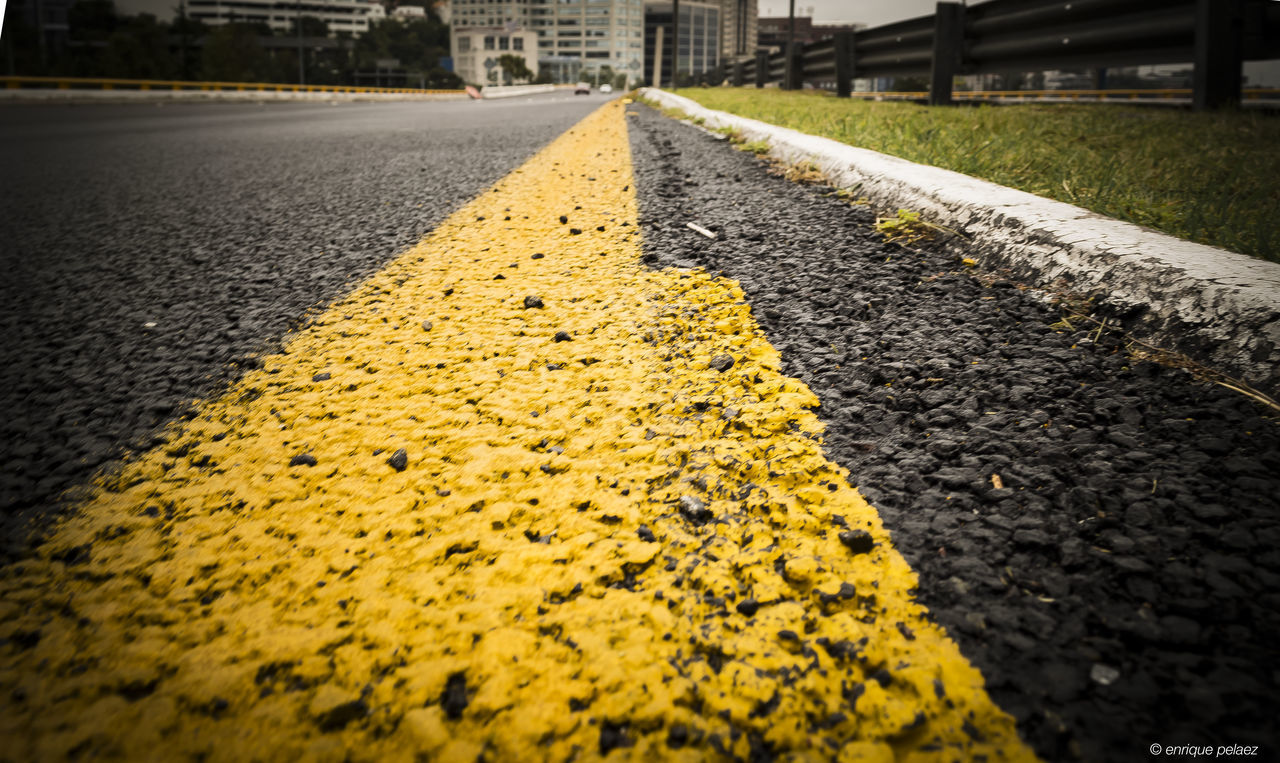 yellow, asphalt, surface level, straight, road, no people, transportation, outdoors, textured, day, city, close-up