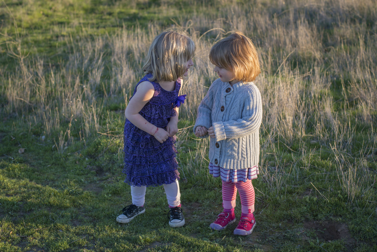 Playful Elementary Sisters Standing On Field