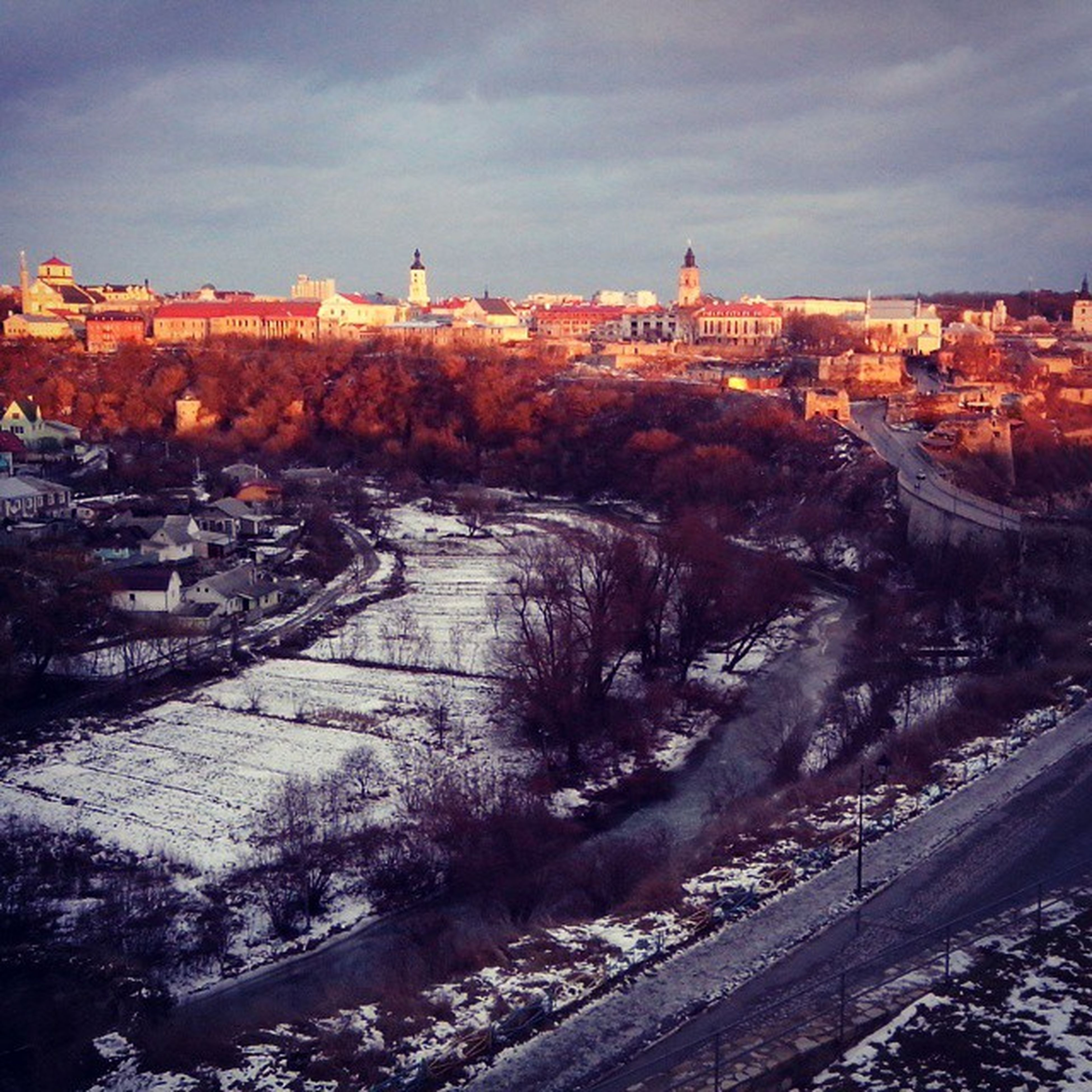 building exterior, architecture, built structure, sky, house, snow, winter, residential structure, season, cold temperature, residential building, town, high angle view, residential district, city, cloud - sky, nature, outdoors, sunset, tree