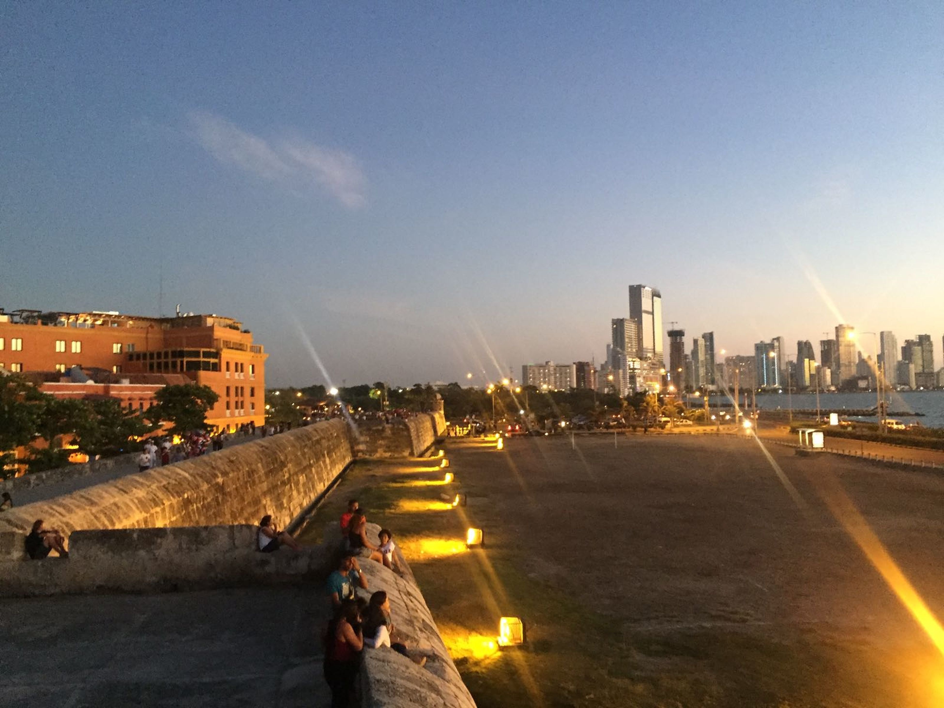 city, architecture, building exterior, built structure, skyscraper, cityscape, urban skyline, sky, illuminated, modern, city life, travel destinations, outdoors, downtown district, night, people