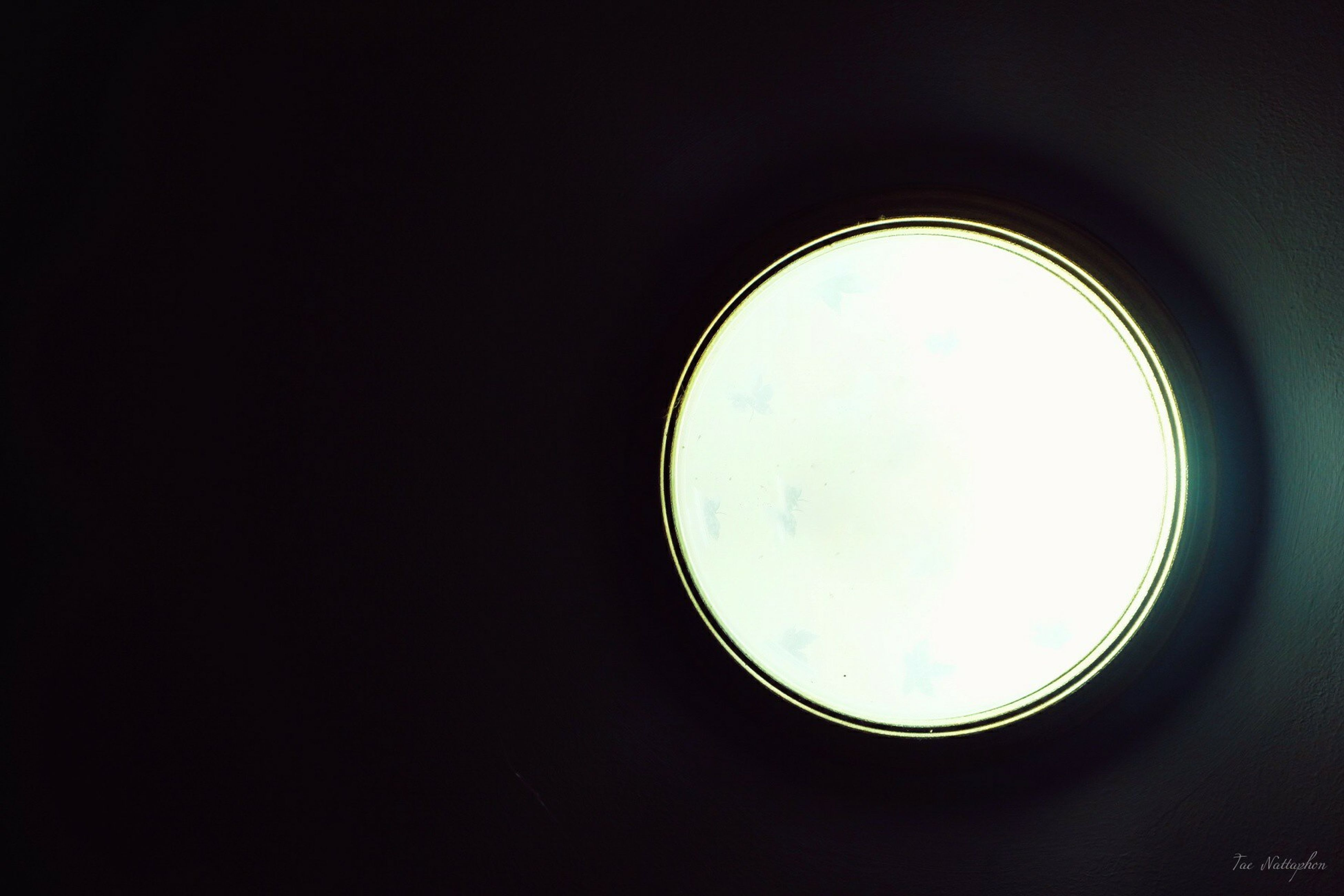 indoors, circle, copy space, window, geometric shape, glass - material, transparent, low angle view, dark, clear sky, shape, close-up, round, no people, reflection, sky, circular, lighting equipment, ceiling, silhouette