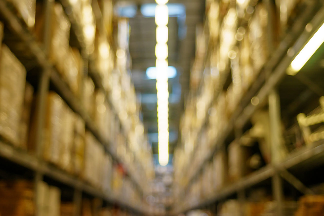 Blurred image inside a warehouse. Abundance Backgrounds Boxes Close-up Compartments Crates Defocused Focus On Foreground Glowing Illuminated In A Row Light Lighting Equipment Lights Lit No People Racks Repetition Rows Selective Focus Side By Side Warehouse