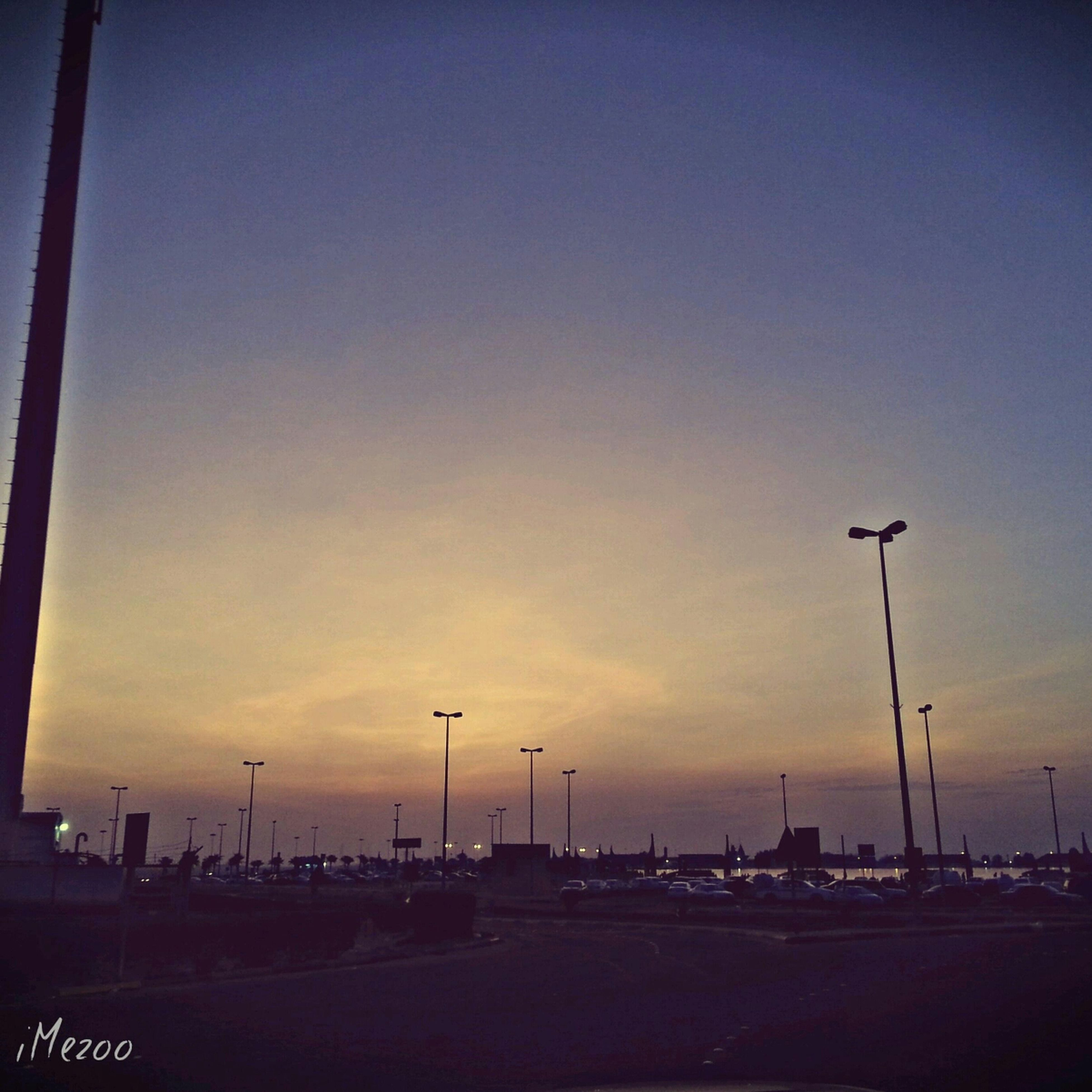 street light, transportation, sunset, sky, road, car, lighting equipment, street, in a row, mode of transport, illuminated, copy space, land vehicle, silhouette, parking lot, built structure, dusk, outdoors, pole, no people