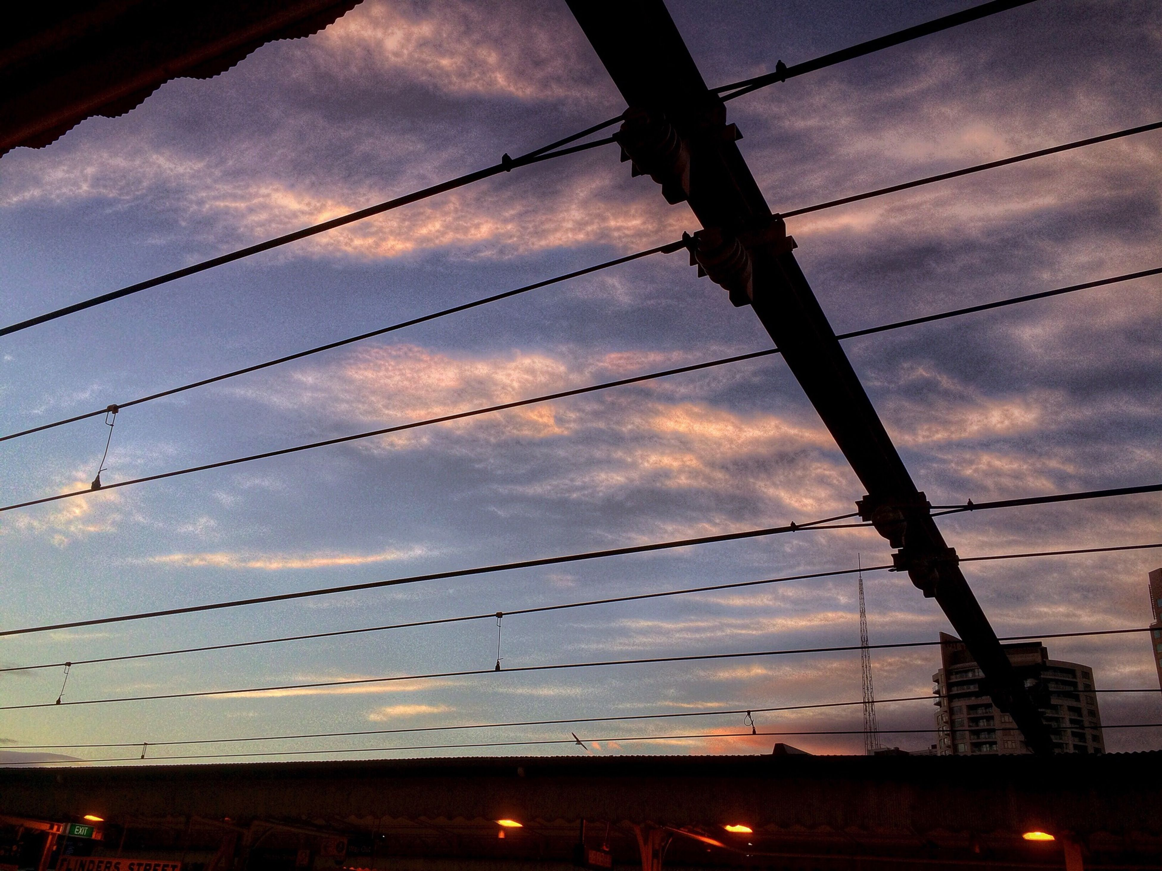 power line, low angle view, sky, cable, electricity, cloud - sky, electricity pylon, power supply, connection, silhouette, cloudy, built structure, cloud, architecture, sunset, power cable, fuel and power generation, dusk, technology, building exterior