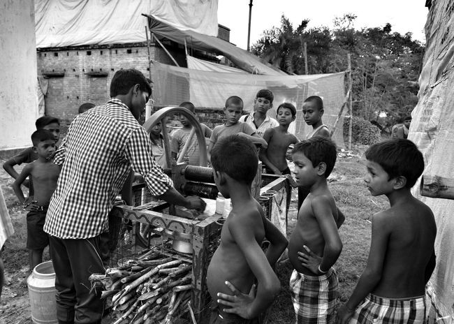 Extracting juice from sugar cane... curious poor village children standing all around... Togetherness Poor Children Kids Village Strugle For Existence Story Of The Marginalised People Village People Non-urban Scene Day Outdoors Standing Village Black & White Photography Street Photography Live From The Street My Country My People