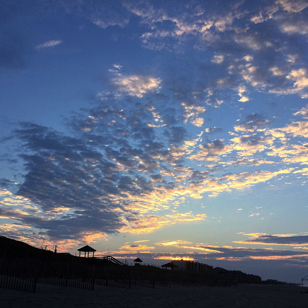 Low Angle View Of Beach Against Sky During Sunset