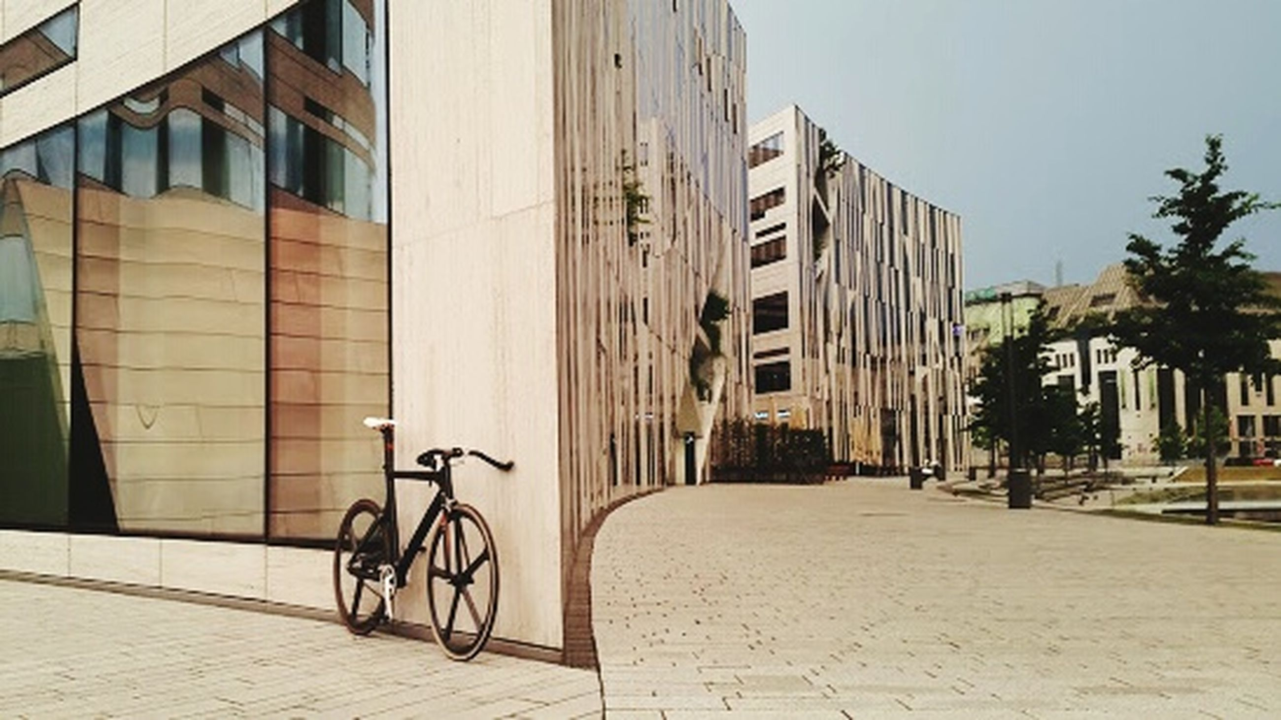architecture, building exterior, built structure, city, bicycle, building, street, window, residential building, transportation, residential structure, sunlight, sidewalk, day, shadow, cobblestone, parking, modern, outdoors, wall - building feature