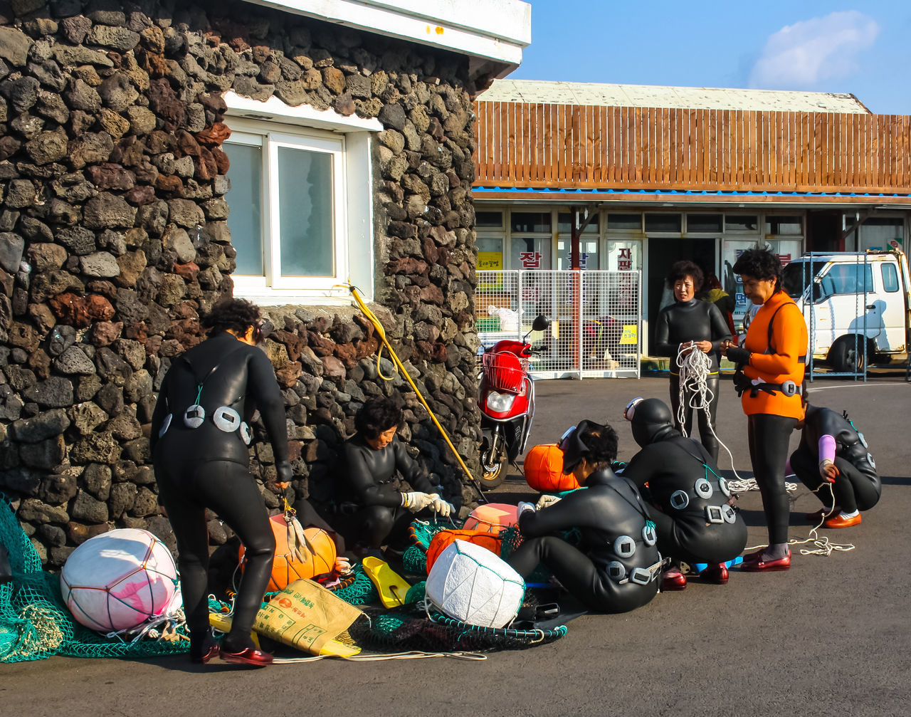 Women diver; Haenyeo at Jeju Island who dive in deep sea without using oxygen tank to search for pearl. Most of them are breadwinner for their family. Architecture Built Structure Casual Clothing City City Life Day Girl Power Haenyeo JEJU ISLAND  Leisure Activity Lifestyles Medium Group Of People Men Outdoors Sky Women Diver People Of The Oceans Girl Power Pearl Breadwinner Dive Working Net Everyday Emotion