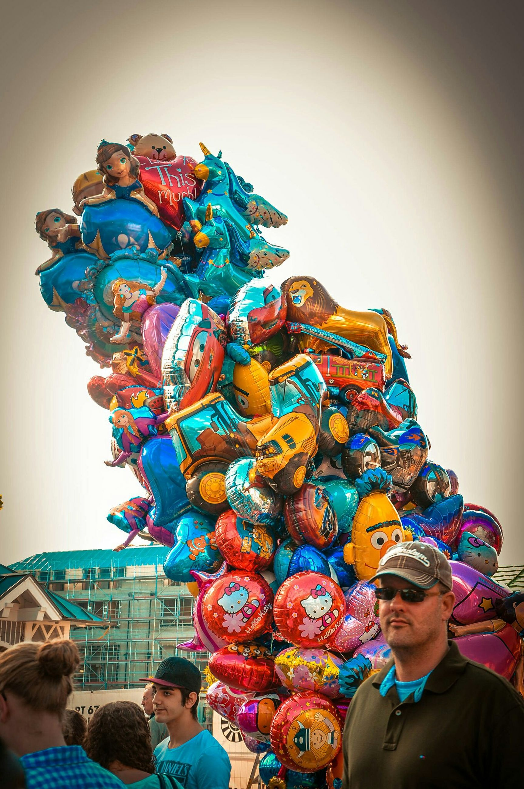 leisure activity, lifestyles, multi colored, childhood, fun, clear sky, copy space, enjoyment, amusement park, arts culture and entertainment, casual clothing, person, happiness, togetherness, amusement park ride, blue, headshot, holding