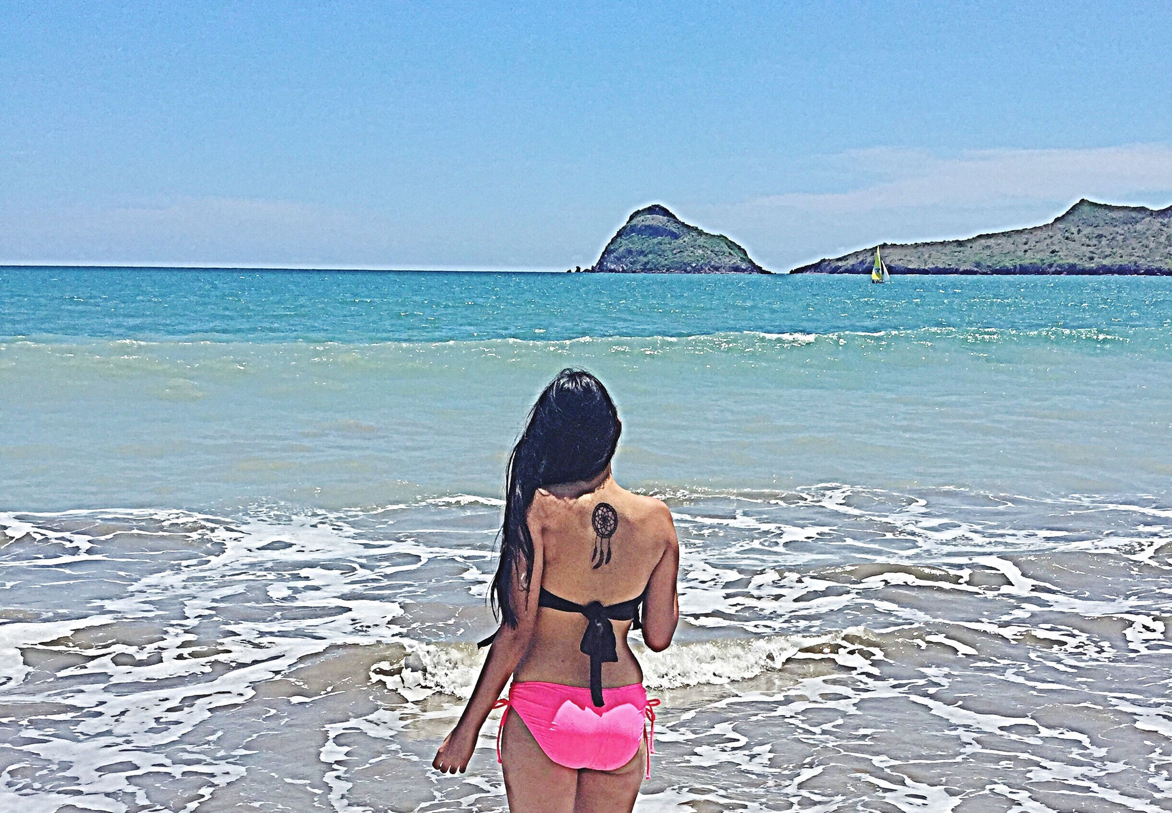 water, standing, lifestyles, sea, leisure activity, rear view, casual clothing, horizon over water, person, sky, three quarter length, scenics, tranquility, vacations, clear sky, waist up, young adult, beach