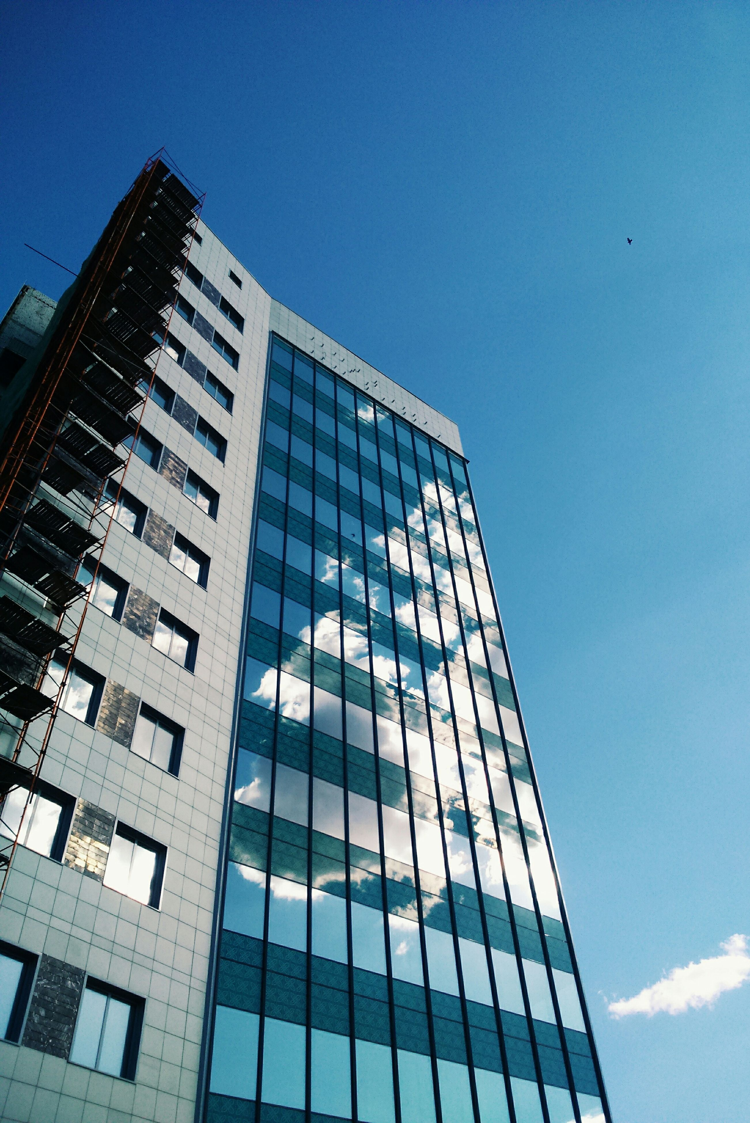 low angle view, architecture, building exterior, built structure, modern, office building, blue, city, glass - material, clear sky, skyscraper, building, tall - high, reflection, tower, sky, window, day, outdoors, no people