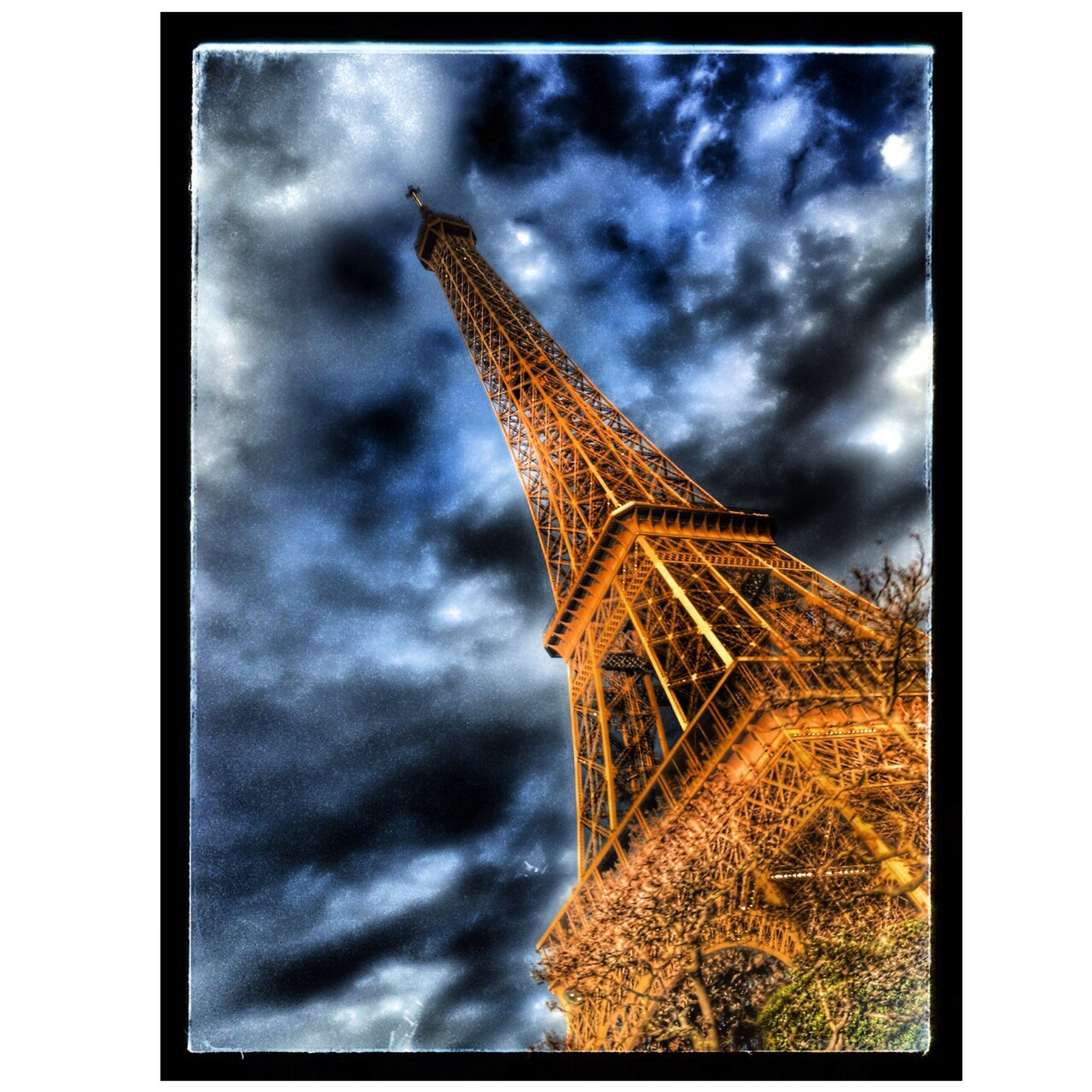 sky, built structure, cloud - sky, low angle view, architecture, cloudy, transfer print, auto post production filter, building exterior, tower, tall - high, cloud, overcast, weather, travel destinations, eiffel tower, famous place, tall, history, outdoors