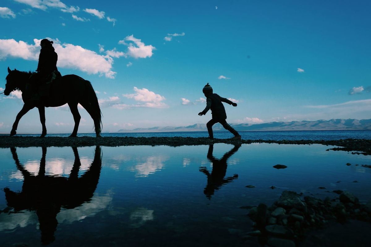 Uncle and niece walk along the shore of the lake.Reflection Water Silhouette Beauty In Nature Outdoors Beach Walking Side View Kyrgyzstan Son Kol Son Kol Lake Son-kol