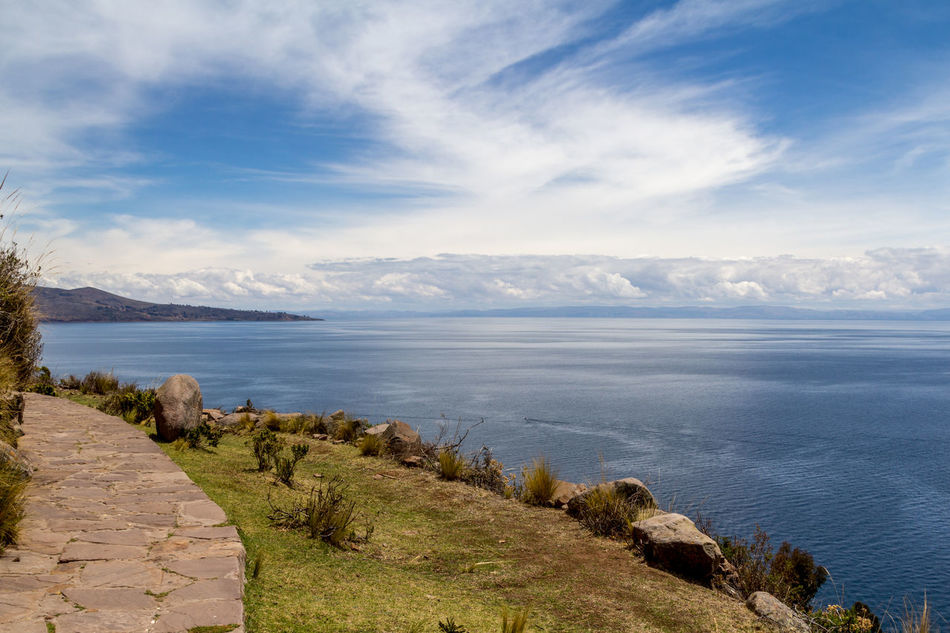Photograph from the top of Taquile island of the blue and calm waters of Titicaca lake in Puno, Peru. Adventure Andes Calm Cloud Enjoy Freedom Grass Holiday Immense Island Lake Landscape Nature Peace Peaceful Peru Peruvian Puno Relax Rocks Sky Taquile Titicaca Travel Water