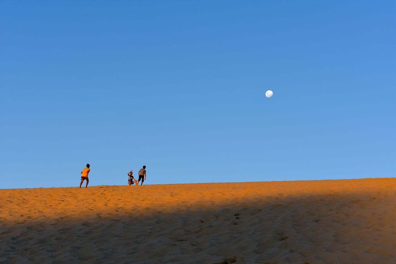 sand, desert, sand dune, arid climate, moon, nature, clear sky, real people, sky, blue, landscape, outdoors, leisure activity, beauty in nature, day, scenics, men, lifestyles, mammal, people