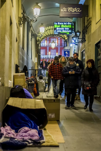 People passing through Calle Mayor, Comentada alley, passing next boxes used by street people, in Madrid, Spain. Box City City Life Comentada Alley Architecture Built Structure Editorial  Evening Illuminated Indoors  Large Group Of People Men Passage People Real People Sleeping Social Issues Street Street People Women