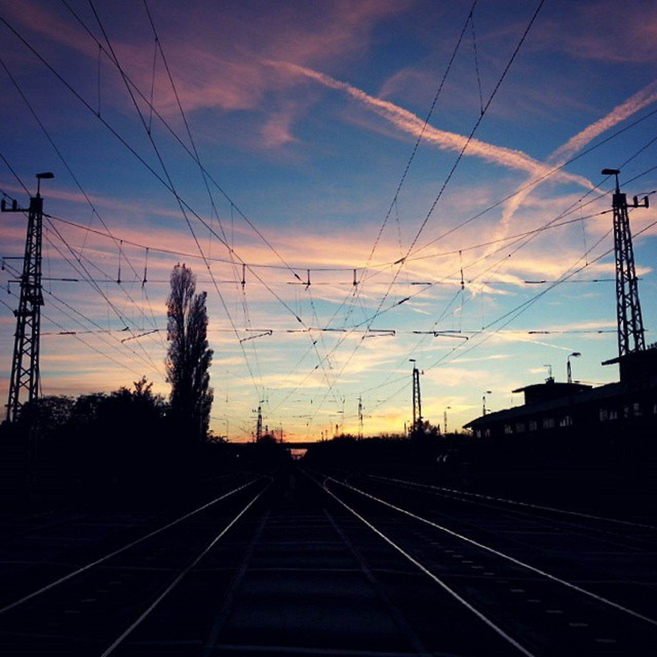 railroad track, cable, rail transportation, sky, transportation, sunset, electricity pylon, power line, cloud - sky, connection, no people, railway track, silhouette, power supply, electricity, outdoors, the way forward, built structure, nature, technology, day, architecture