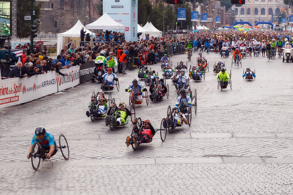 Rome, Italy - April 2, 2017: hand cycle, the departure of the athletes on Via dei Fori Imperiali, the Coliseum on background. Adult Bicycle; City Crowd Day Handcycle High Angle View Large Group Of People Marathon Mode Of Transport Outdoors People Real People Rome Marathon Rome Marathon 2017 Rome Marathon 23rd Special Cycle Sports Race Starting Line Transportation