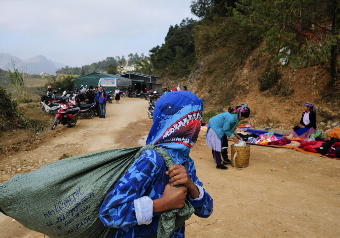 A boy in modern costume goes to the traditional market of ethnic minority people. Ha Giang, Viet Nam, 2016 #boy #culture #modern #shark #traditional Adult Adventure Mountain Nature Outdoors Real People Women
