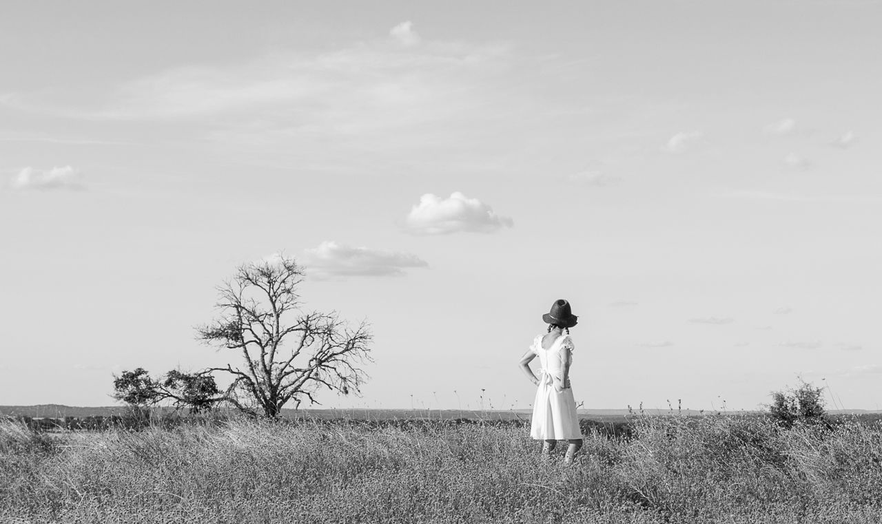 one person, field, sky, real people, standing, cloud - sky, leisure activity, nature, outdoors, full length, rear view, grass, day, women, casual clothing, young adult, lifestyles, tree, landscape, fashion, young women, bare tree, beauty in nature, fashion model, wedding dress, bride, adult, people